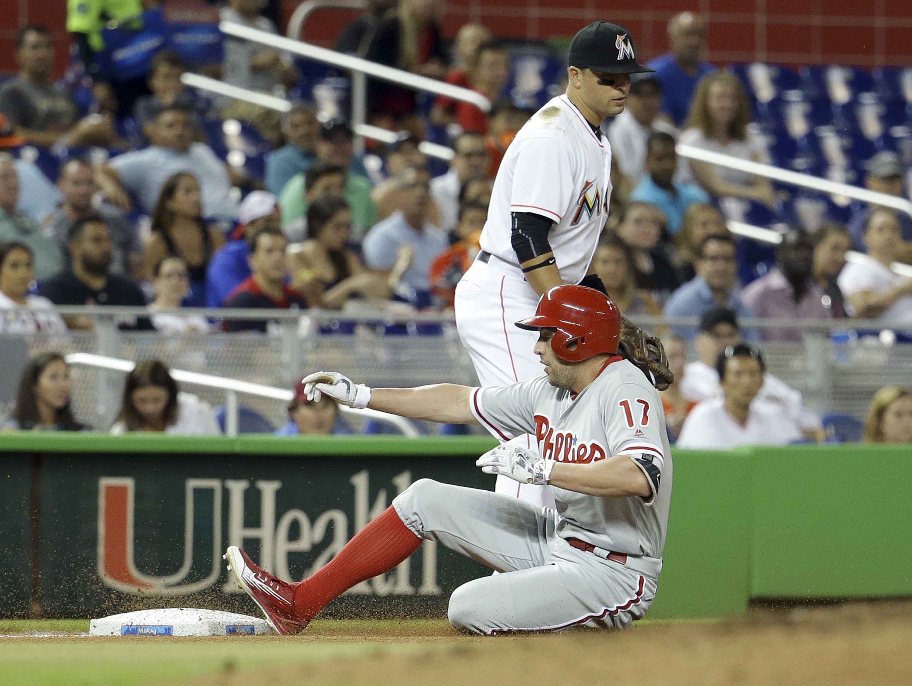 Philadelphia Phillies' Peter Bourjos (17) is safe at third with a triple as Miami Marlins third baseman Martin Prado looks on during the fifth inning of a baseball game, Monday, Sept. 5, 2016, in Miami. (AP Photo/Lynne Sladky)