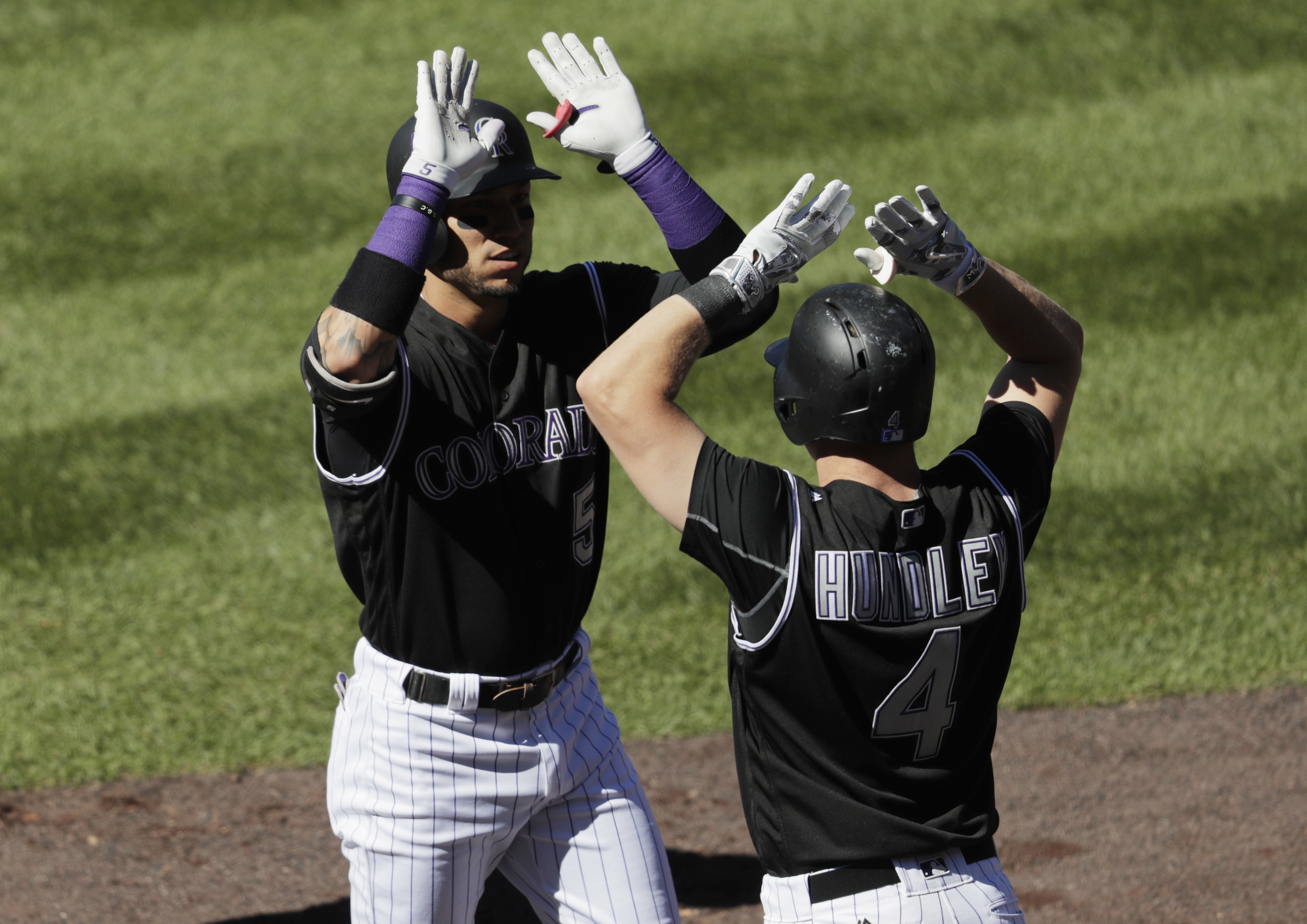 Colorado Rockies' Carlos Gonzalez, left, is congratulated by Nick Hundley after Gonzalez hit a grand slam off San Francisco Giants starting pitcher Matt Moore during the third inning of a baseball game Monday, Sept. 5, 2016, in Denver. (AP Photo/David Zal