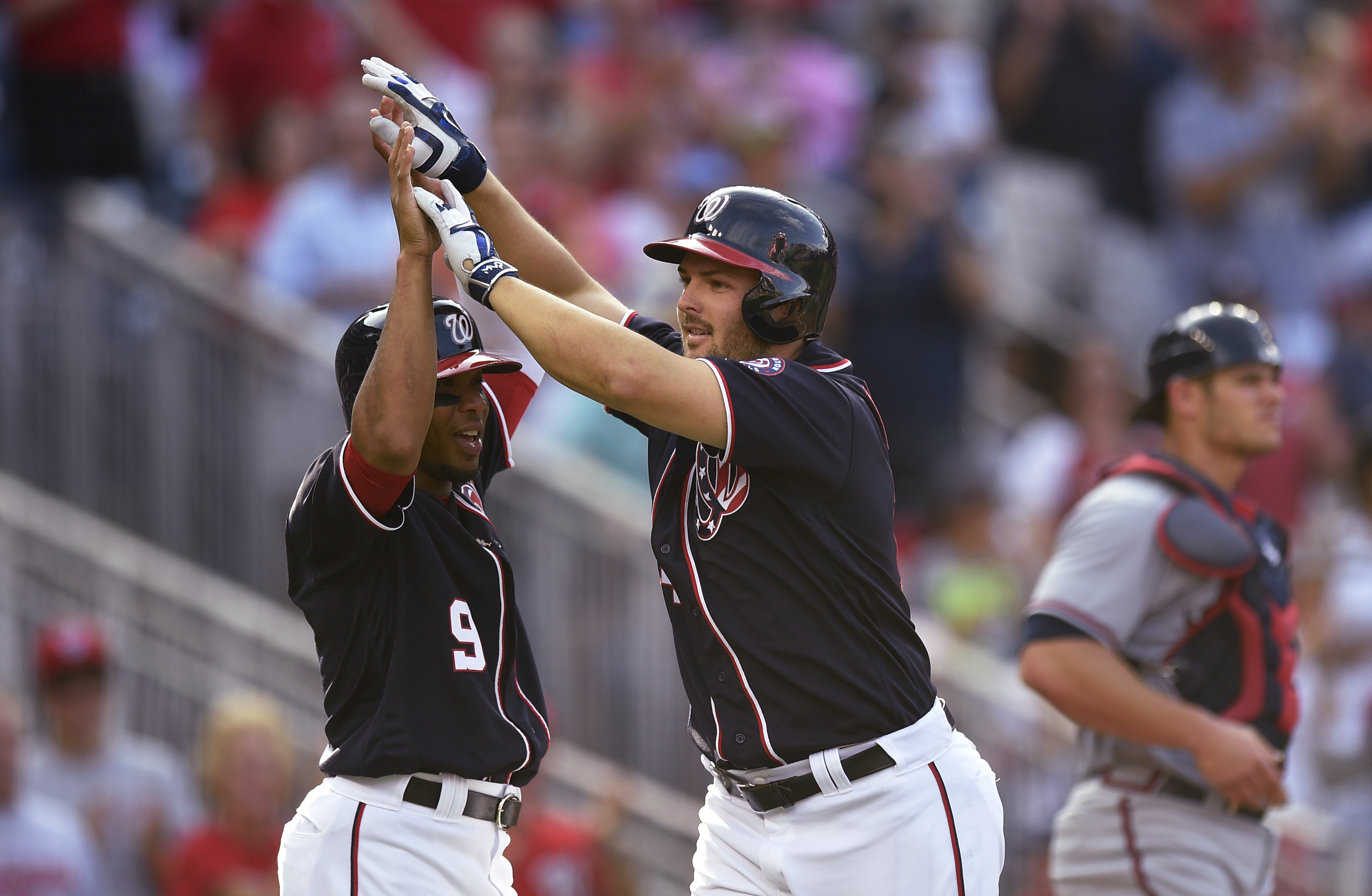Washington Nationals' Chris Heisey, center celebrates his three-run home run with Ben Revere during the third inning of a baseball game, as the Atlanta Braves catcher Anthony Recker waits, Monday, Sept. 5, 2016, in Washington. (AP Photo/Nick Wass)