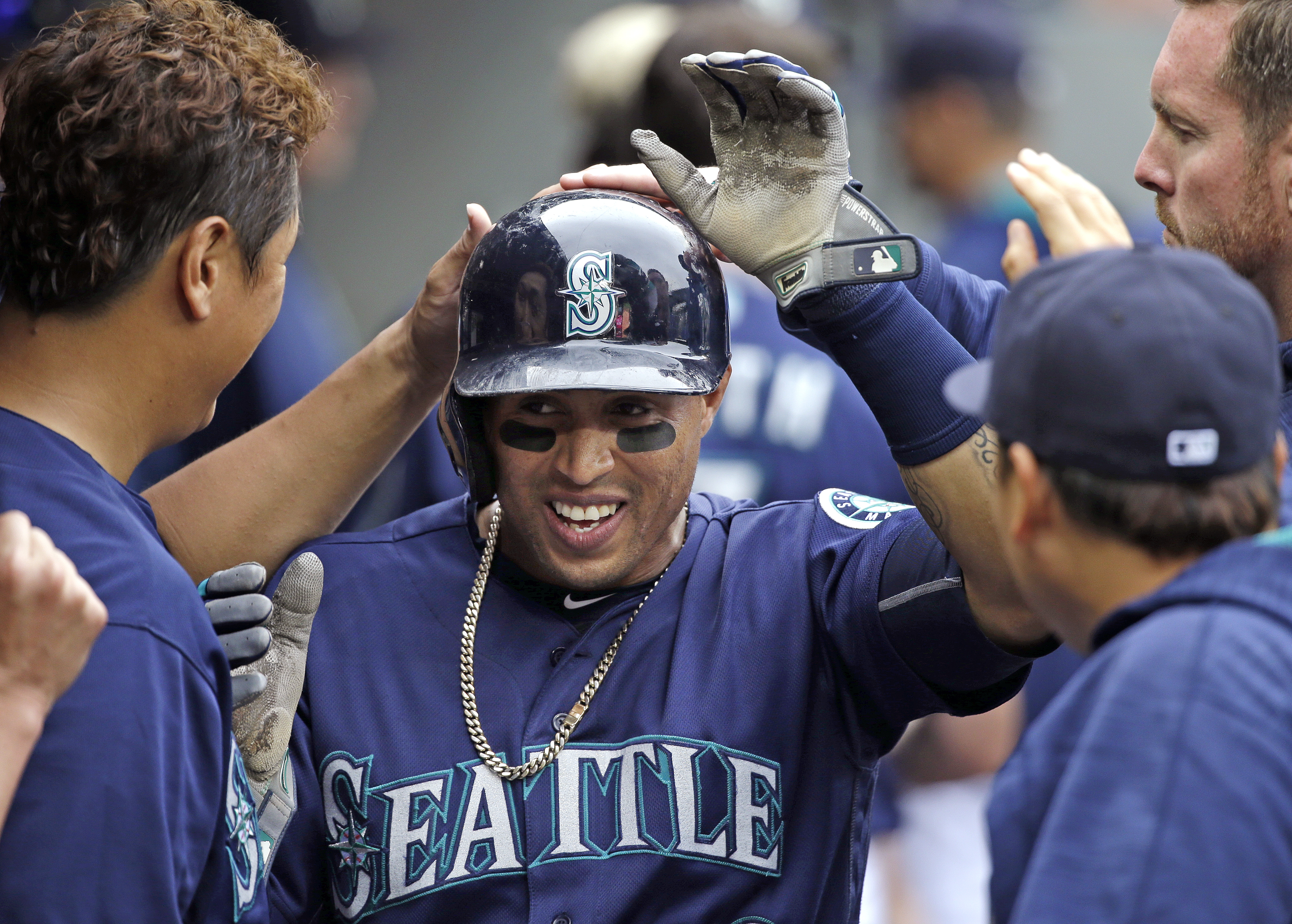 Seattle Mariners' Leonys Martin is congratulated by teammates after scoring against the Texas Rangers during the sixth inning of a baseball game Monday, Sept. 5, 2016, in Seattle. (AP Photo/Elaine Thompson)