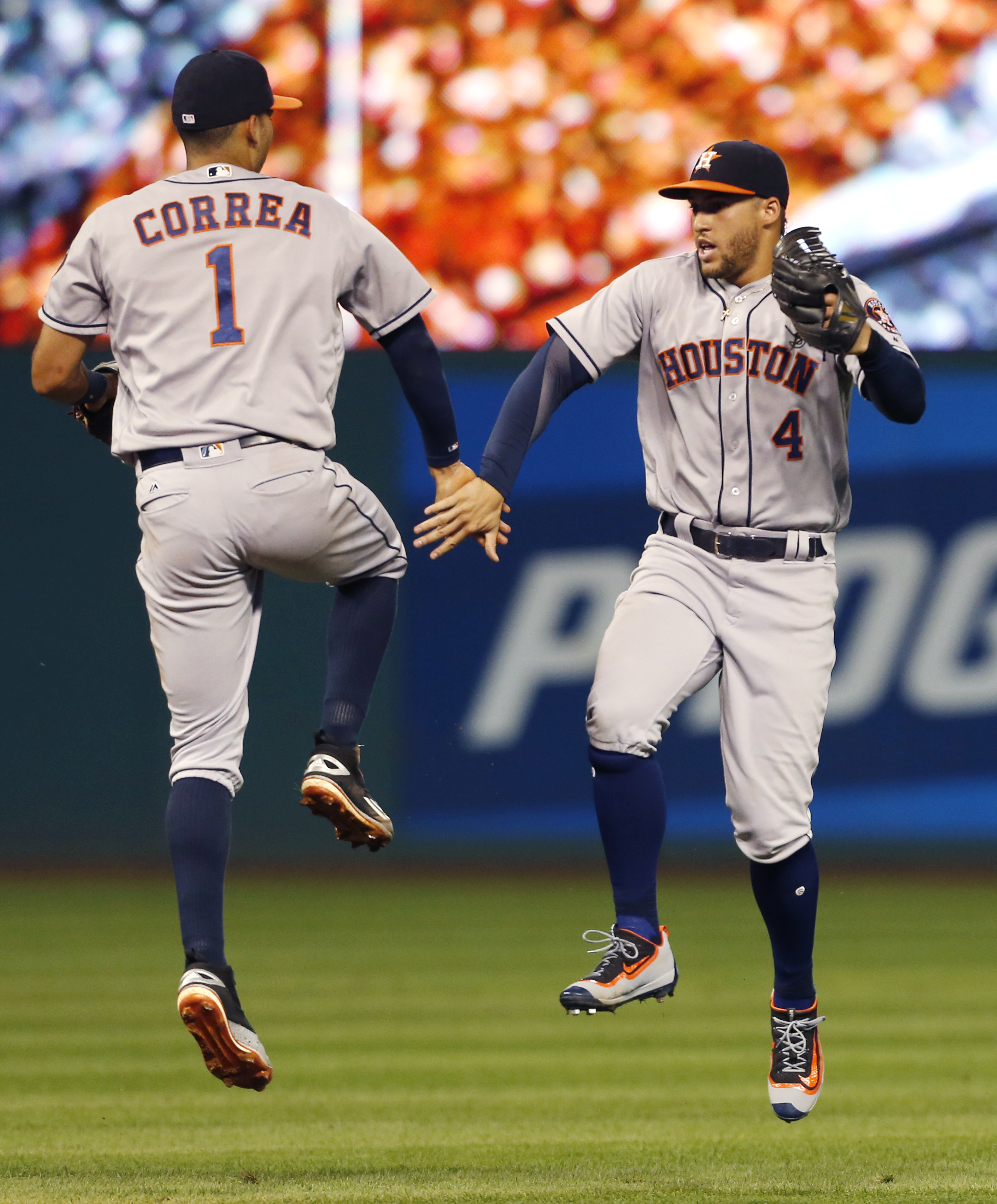 Houston Astros' George Springer (4) and Carlos Correa (1) celebrate the team's 4-3 win over the Cleveland Indians in a baseball game Tuesday, Sept. 6, 2016, in Cleveland. (AP Photo/Ron Schwane)