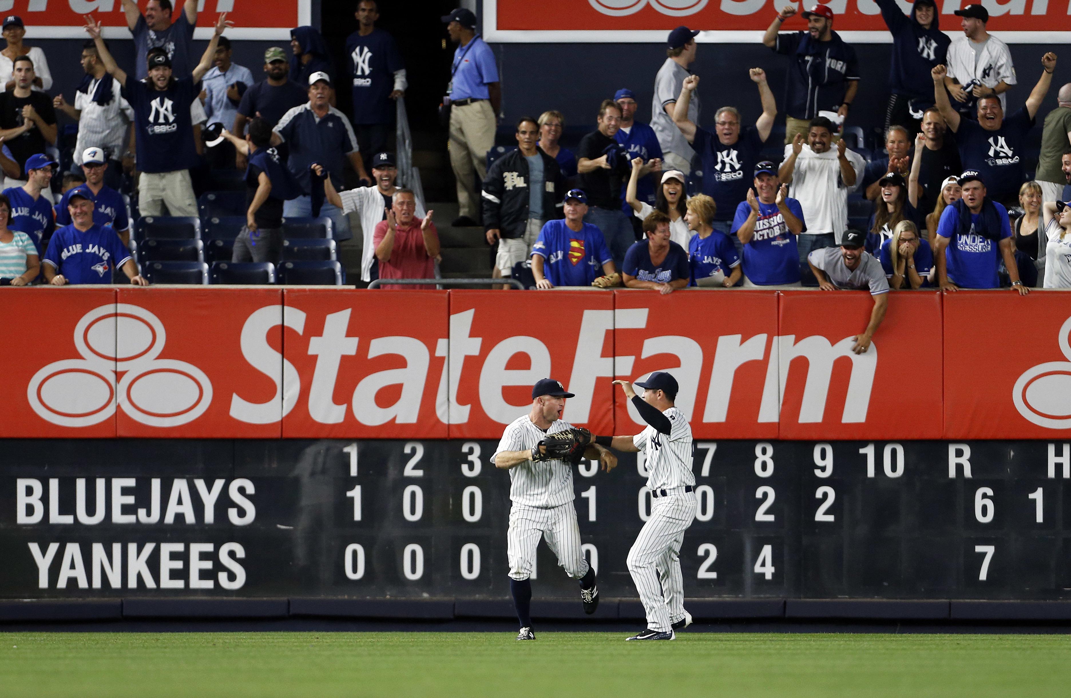 New York Yankees left fielder Brett Gardner, left, celebrates making the game-ending catch with center fielder Jacoby Ellsbury during the ninth inning of a baseball game against the Toronto Blue Jays on Tuesday, Sept. 6, 2016, in New York. The Yankees won