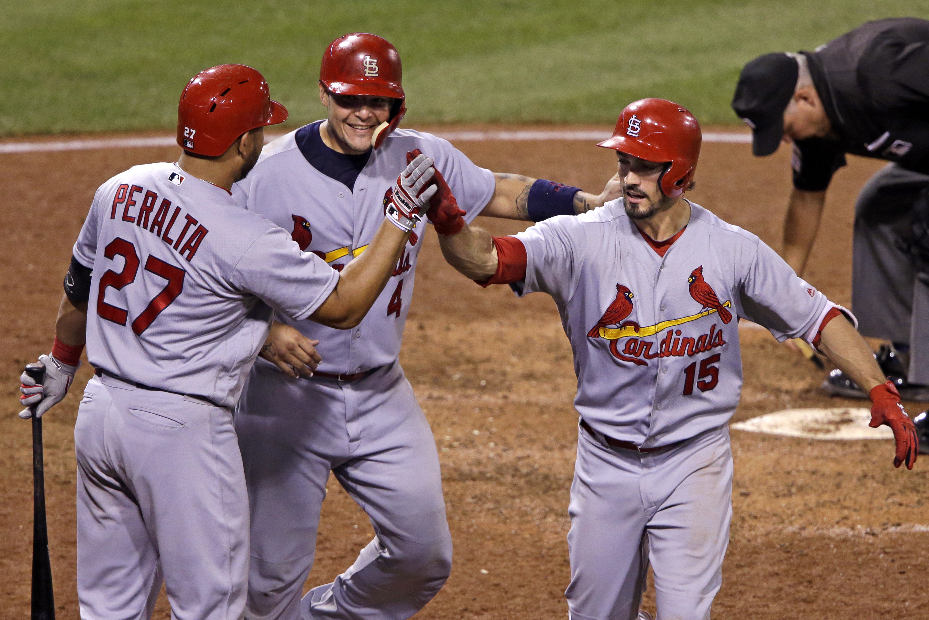 St. Louis Cardinals' Randal Grichuk (15) celebrates with teammates Yadier Molina, center, and Jhonny Peralta (27) after hitting a two-run home run off Pittsburgh Pirates relief pitcher Tony Watson during the ninth inning of a baseball game in Pittsburgh,