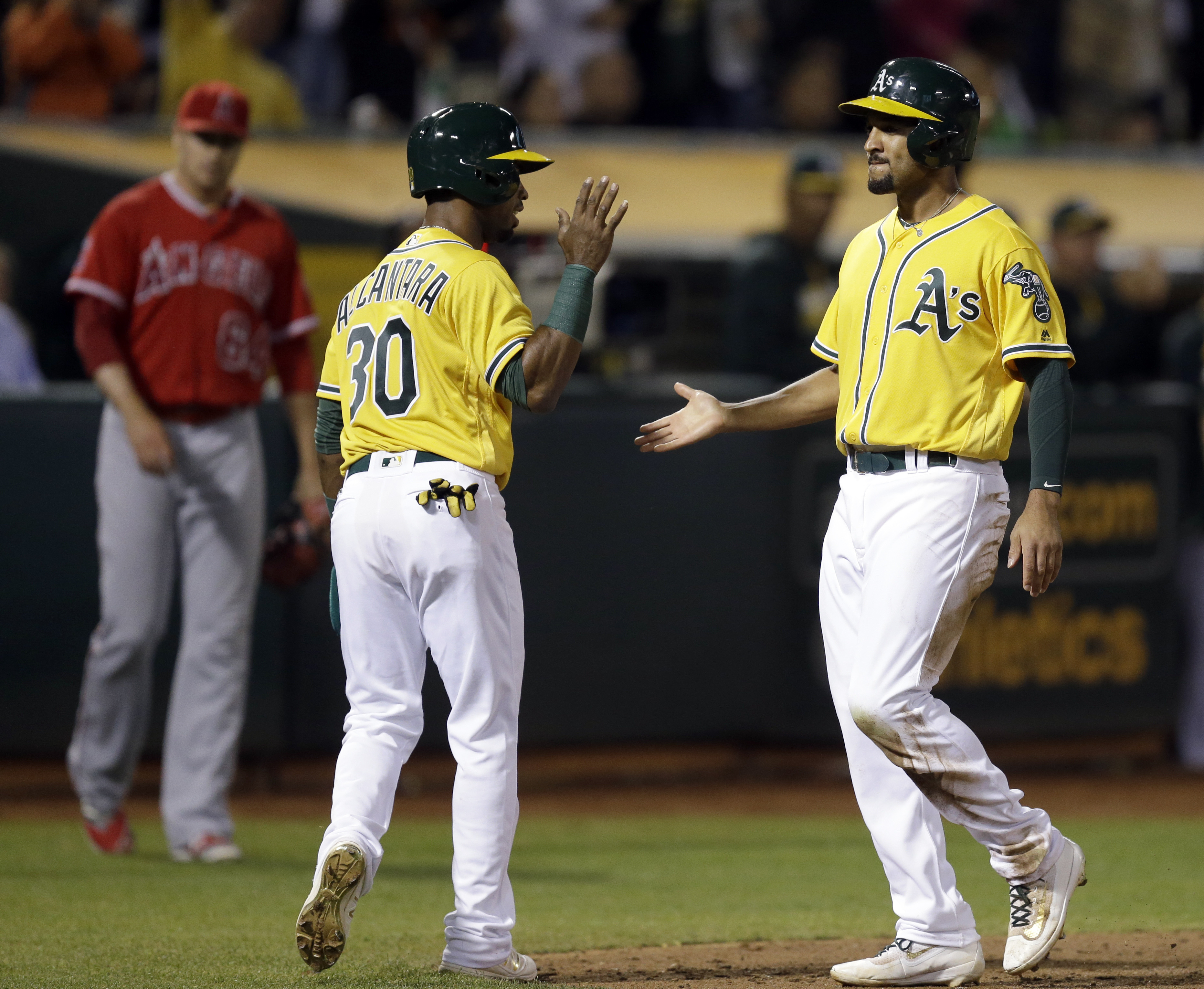 Oakland Athletics' Marcus Semien, right, celebrates with Arismendy Alcantara (30) after scoring against the Los Angeles Angels during the eighth inning of a baseball game Tuesday, Sept. 6, 2016, in Oakland, Calif.  (AP Photo/Ben Margot)