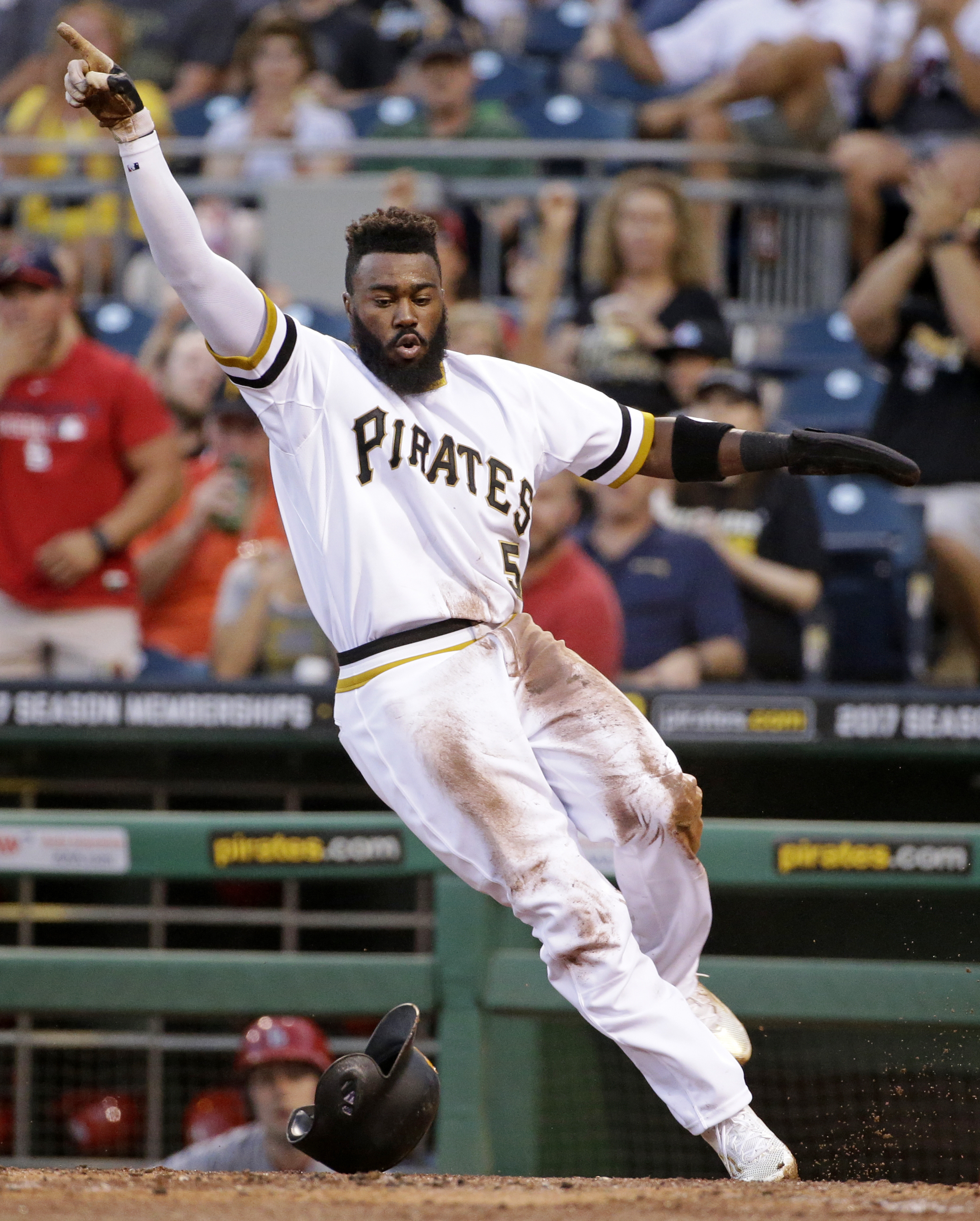 Pittsburgh Pirates' Josh Harrison celebrates after scoring around the tag of St. Louis Cardinals catcher Yadier Molina during the first inning of a baseball game in Pittsburgh, Wednesday, Sept. 7, 2016. (AP Photo/Gene J. Puskar)