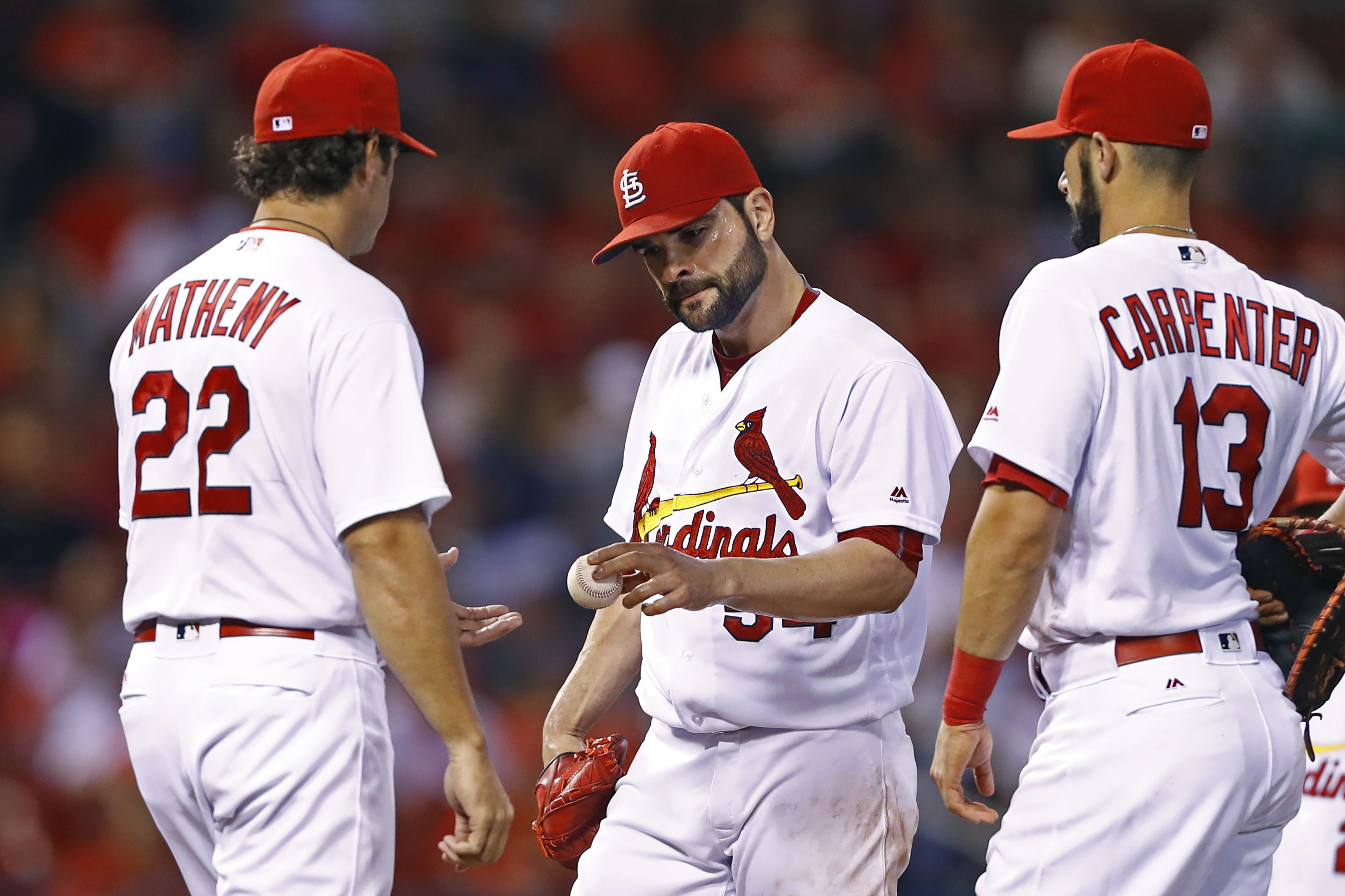St. Louis Cardinals starting pitcher Jaime Garcia, center, hands the ball over to manager Mike Matheny, as Matt Carpenter watches during the fourth inning of a baseball game against the Milwaukee Brewers, Thursday, Sept. 8, 2016, in St. Louis. (AP Photo/B