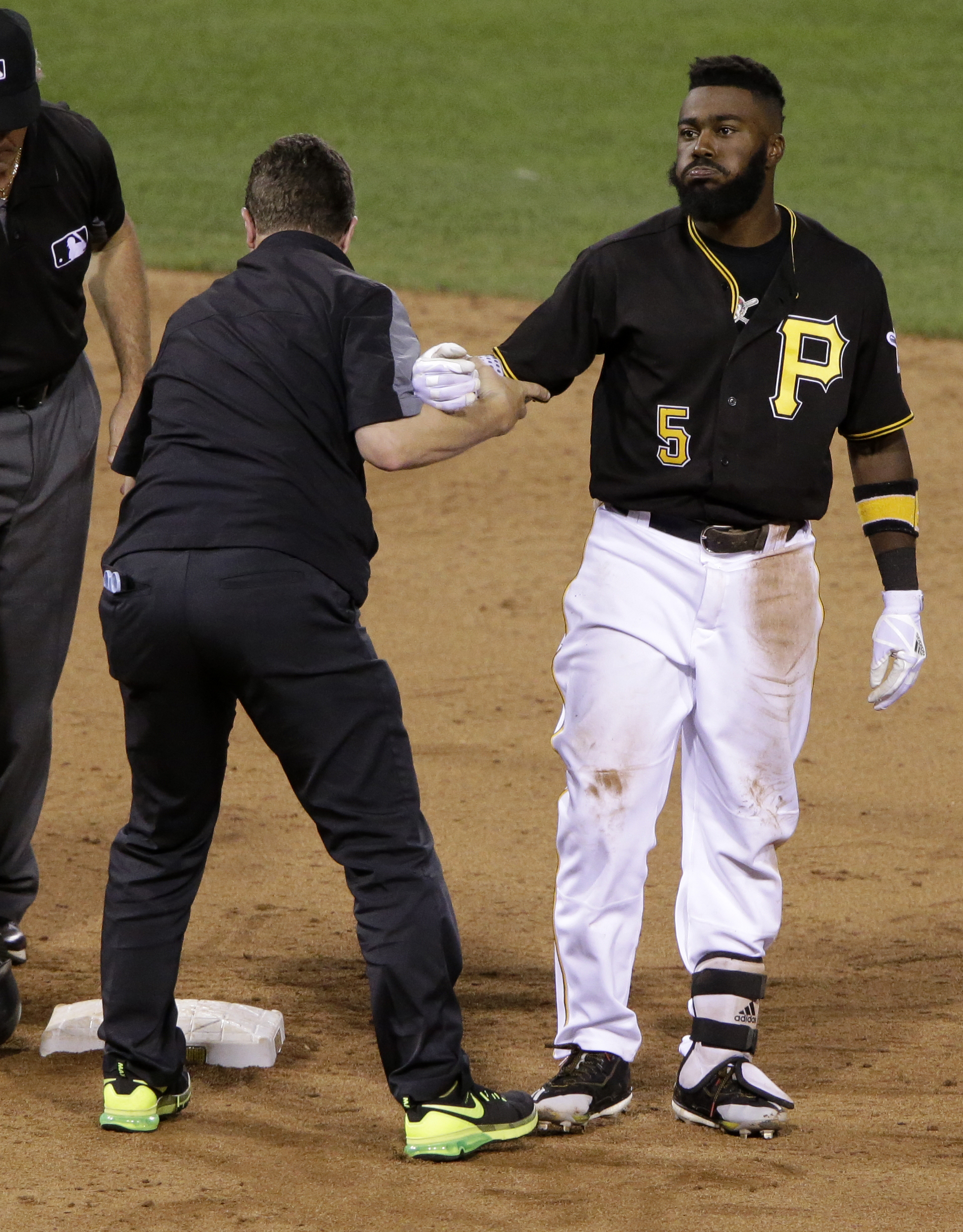 Pittsburgh Pirates' Josh Harrison (5) is helped up by a team trainer after driving in two runs with a double off Cincinnati Reds pitcher Josh Smith in the sixth inning of a baseball game in Pittsburgh, Saturday, Sept. 10, 2016. Harrison was injured on the