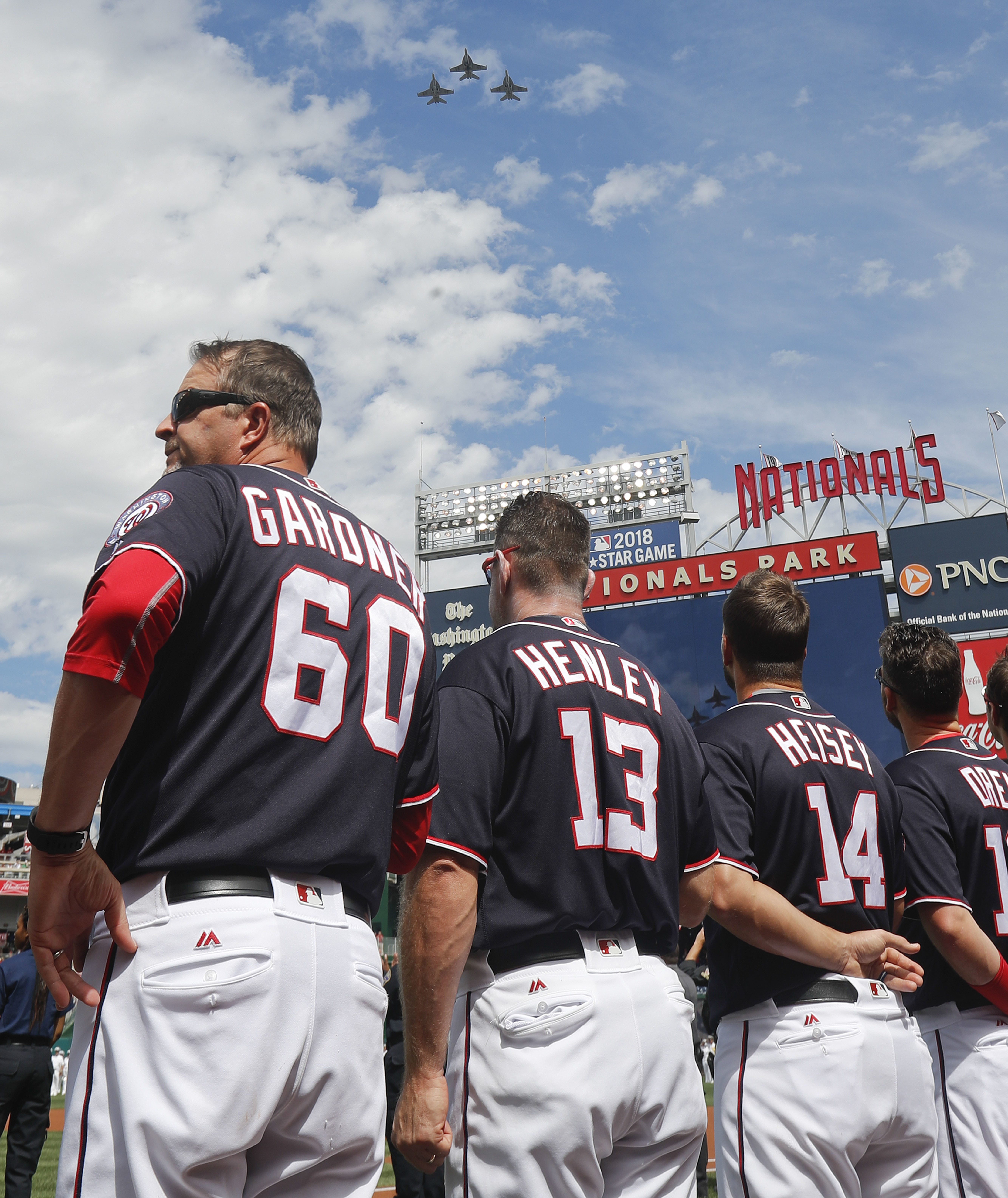 Members of the Washington Nationals watch a fly-over during pregame ceremonies before the start of a baseball game against the Philadelphia Phillies at Nationals Park, Sunday, Sept. 11, 2016 in Washington. The Nationals honored those who died in the attac