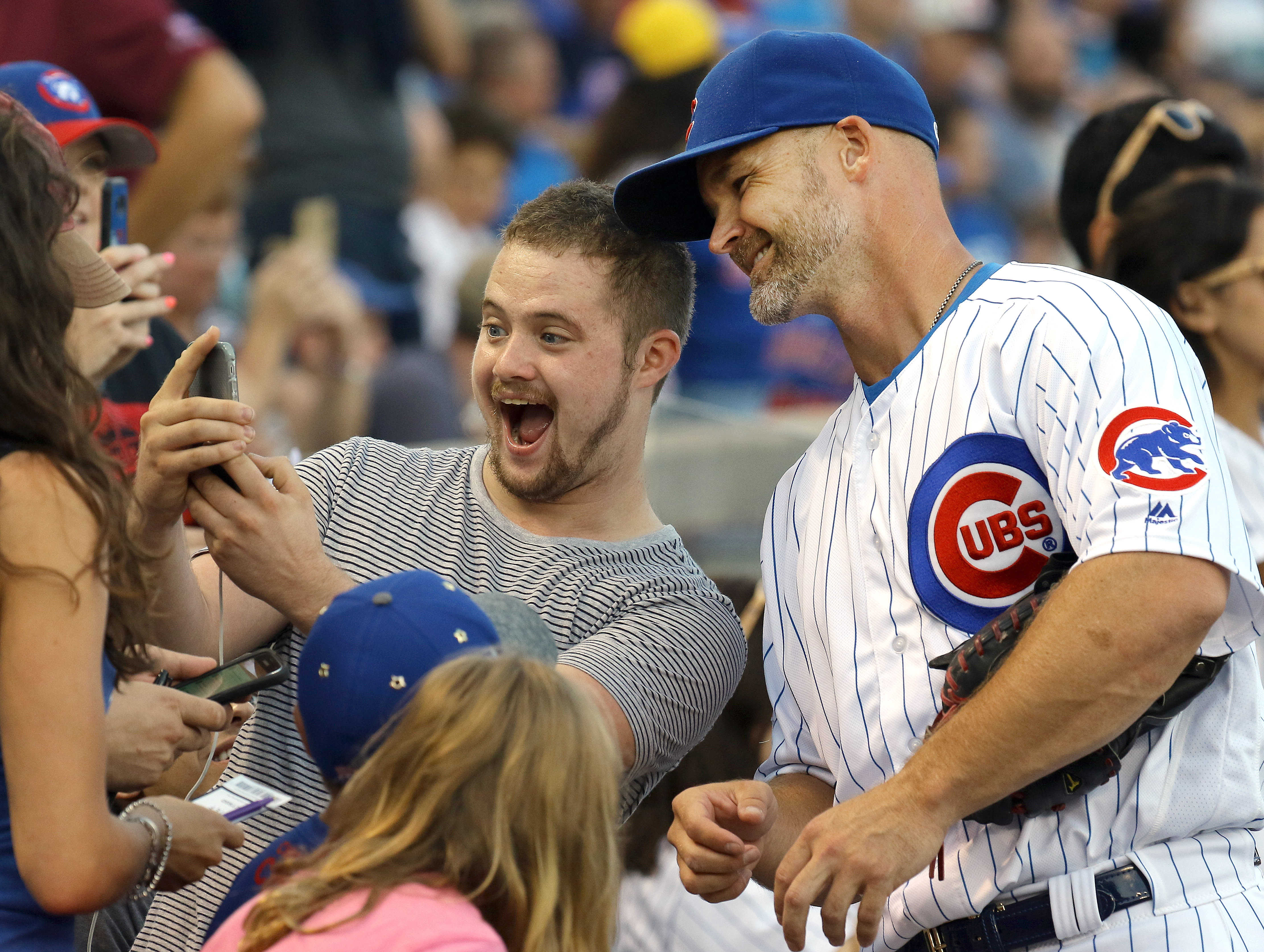 FILE - In this Aug. 30, 2016, file photo, a fan takes a selfie with Chicago Cubs' David Ross before a baseball game in Chicago. The most popular grandpa in Chicago these days just might be the 39-year-old Ross who plays for the most dominant team in the m
