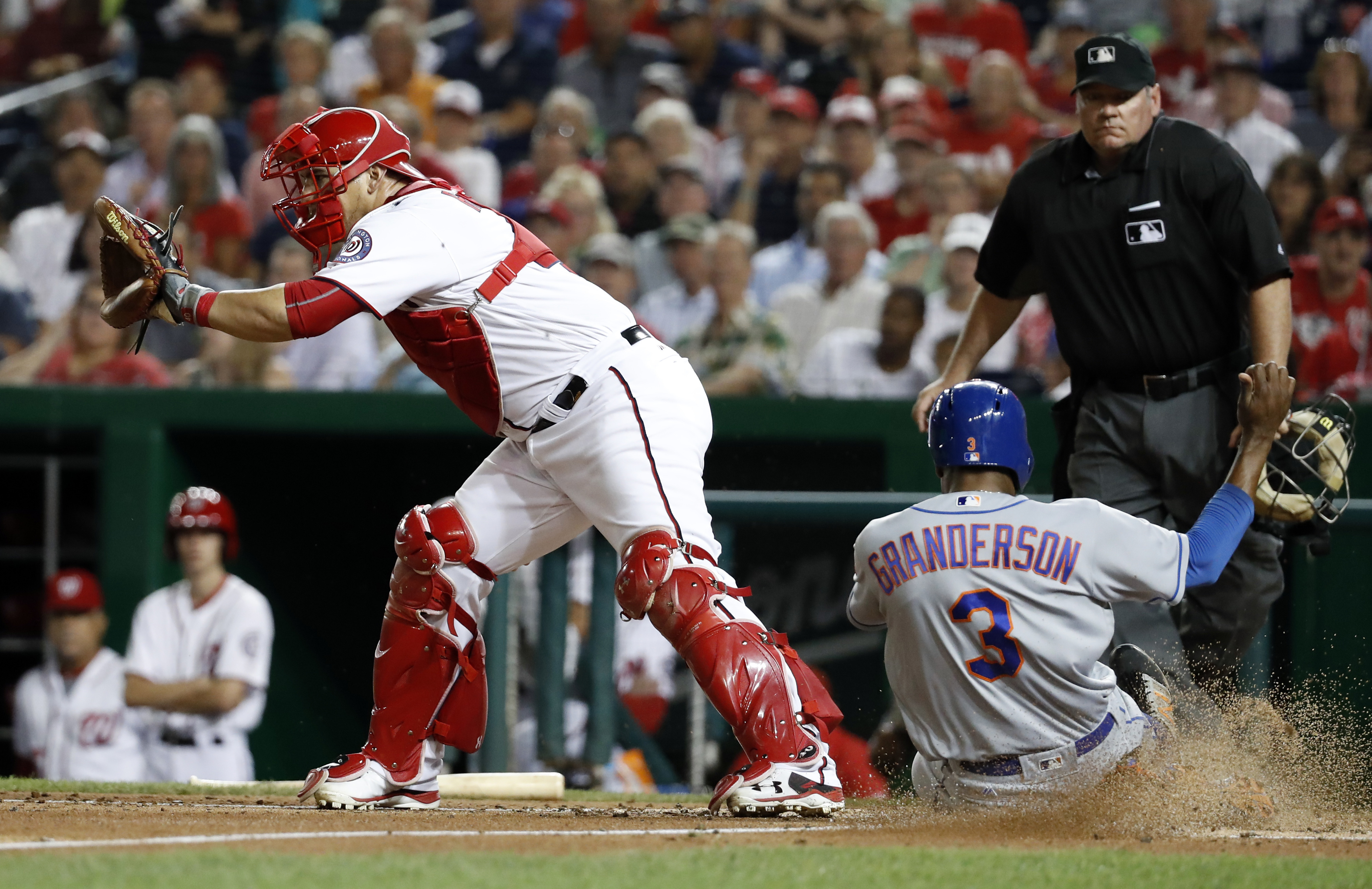New York Mets' Curtis Granderson (3) scores off T.J. Rivera's sacrifice fly as Washington Nationals catcher Wilson Ramos (40) waits for the throw during the fifth inning of a baseball game at Nationals Park, Tuesday, Sept. 13, 2016, in Washington. (AP Pho