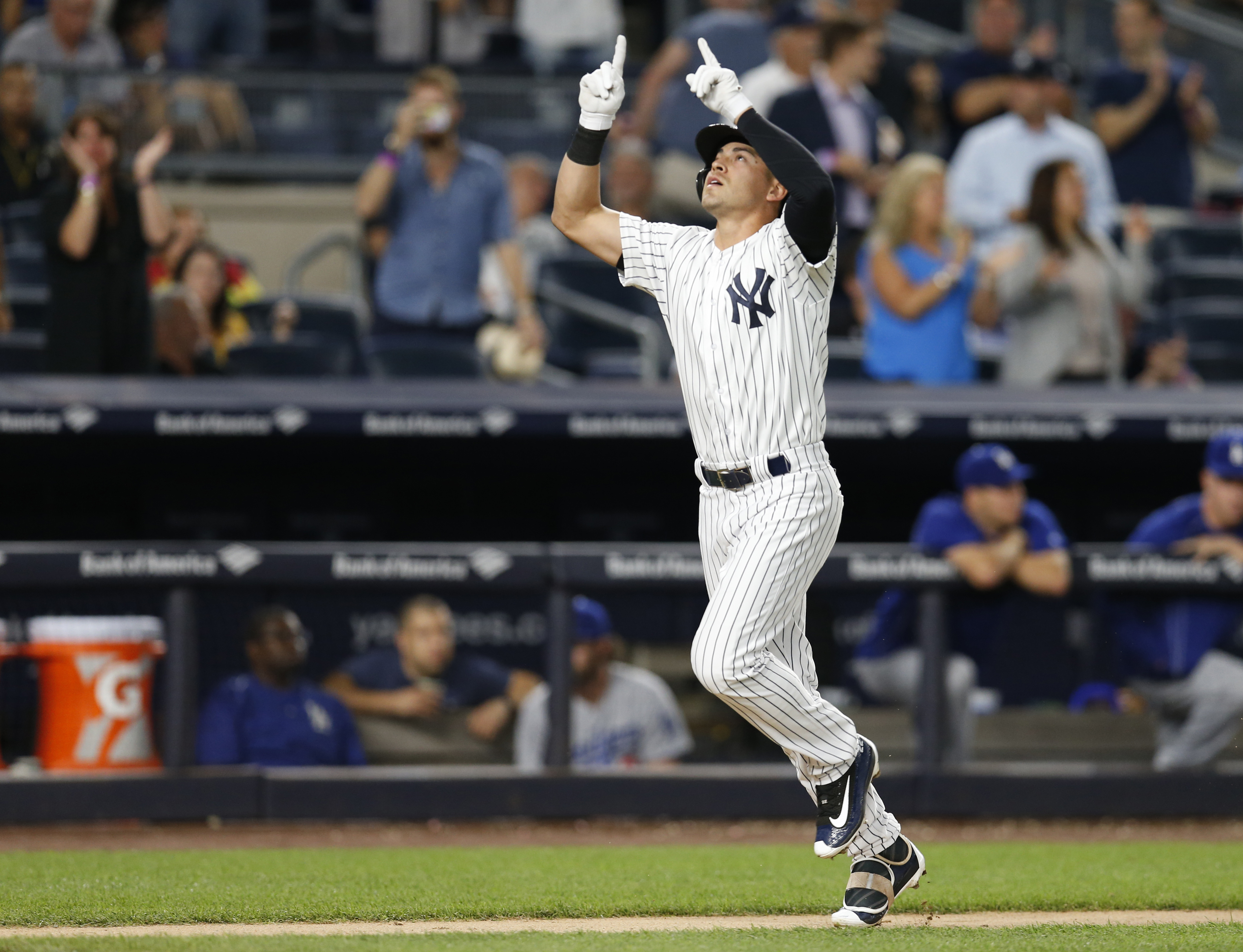 New York Yankees pinch-hitter Jacoby Ellsbury points skyward  as he scores on a seventh-inning solo home run against the Los Angeles Dodgers in a baseball game in New York, Tuesday, Sept. 13, 2016. (AP Photo/Kathy Willens)