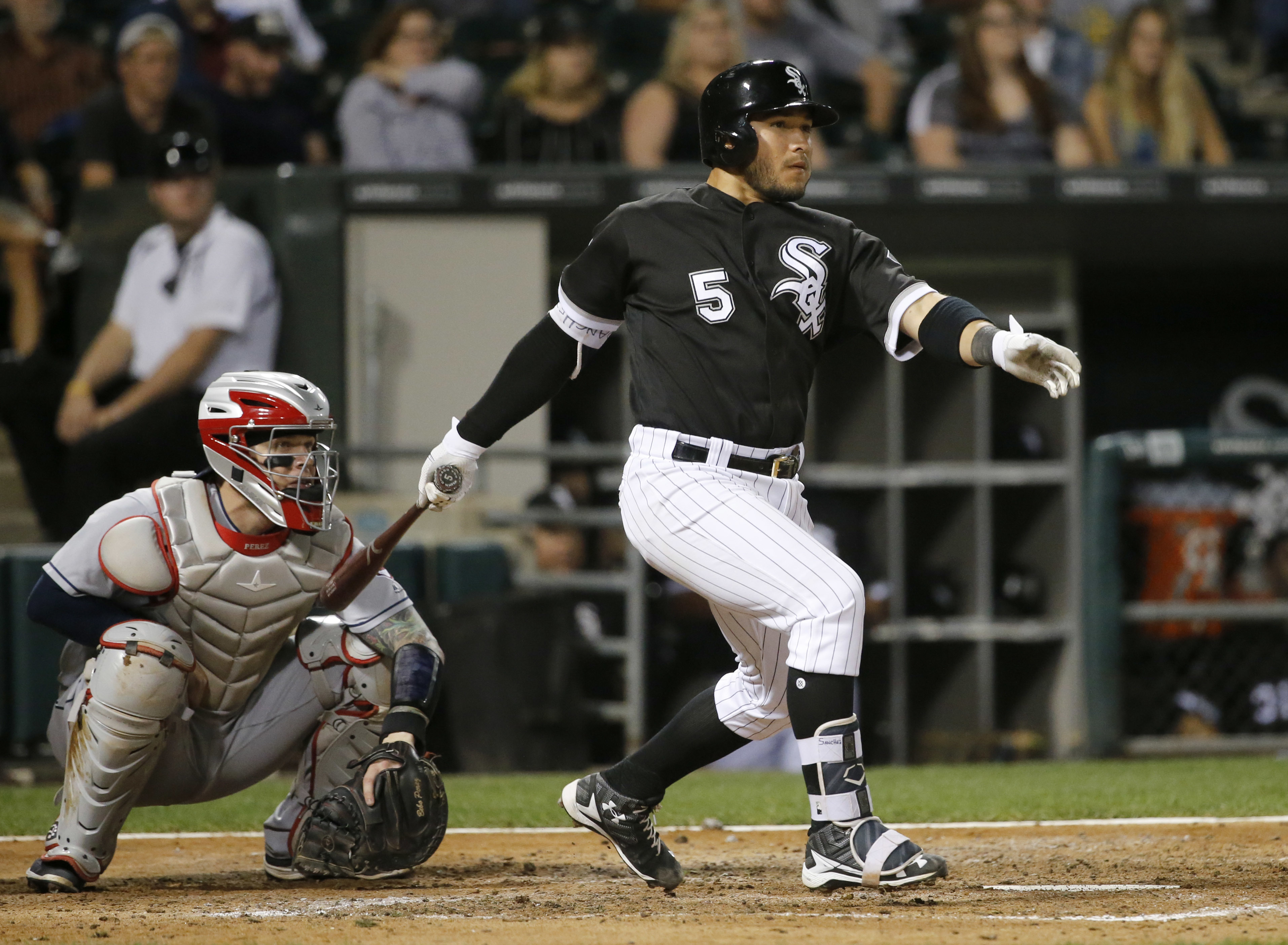 Chicago White Sox's Carlos Sanchez (5) watches his two-run triple off Cleveland Indians relief pitcher Dan Otero with catcher Roberto Perez, scoring Todd Frazier, Avisail Garcia, during the sixth inning of a baseball game, Tuesday, Sept. 13, 2016, in Chic