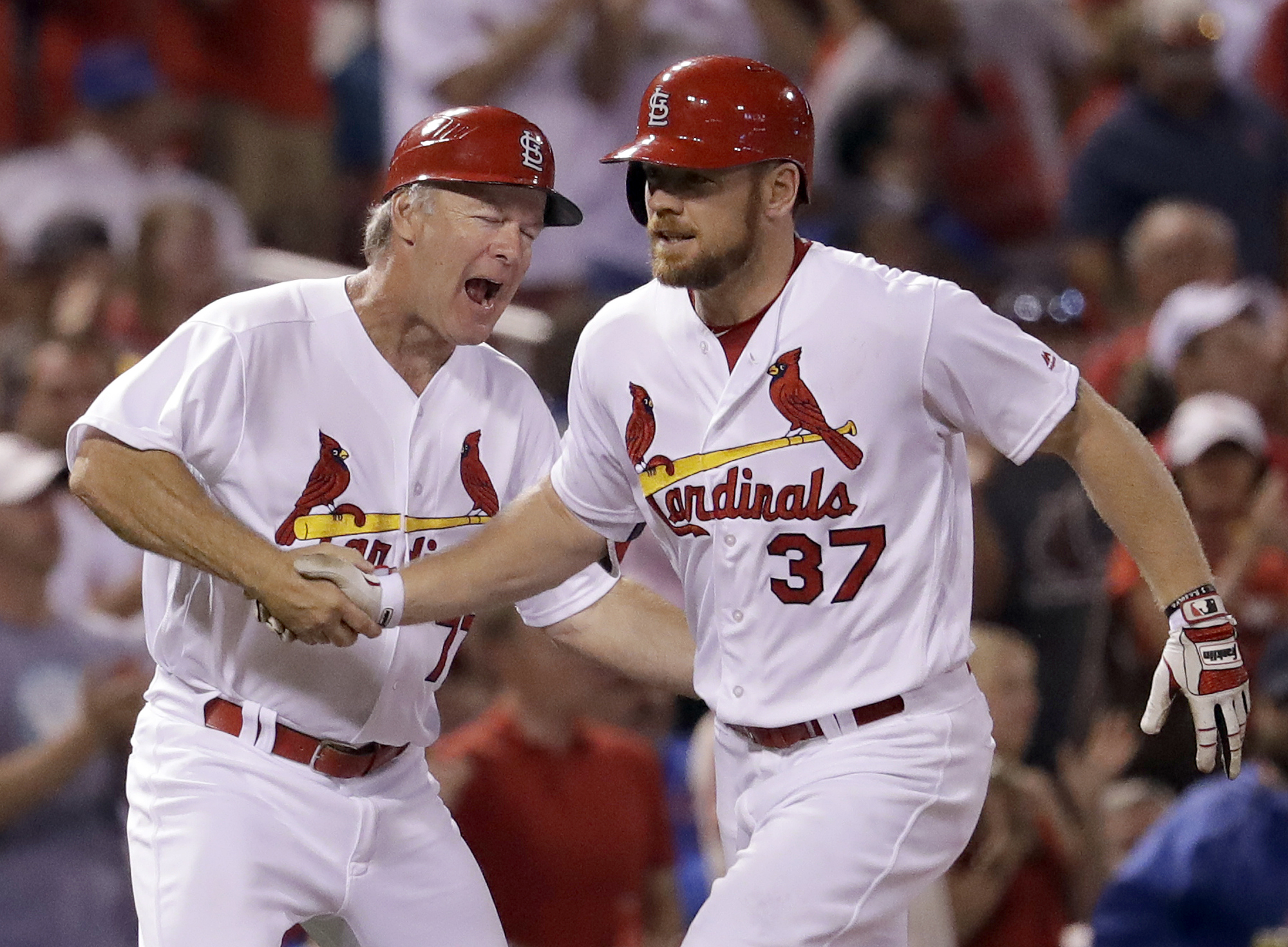 St. Louis Cardinals' Brandon Moss, right, is congratulated by third base coach Chris Maloney while rounding the bases after hitting a two-run home run during the sixth inning of a baseball game against the Chicago Cubs, Tuesday, Sept. 13, 2016, in St. Lou