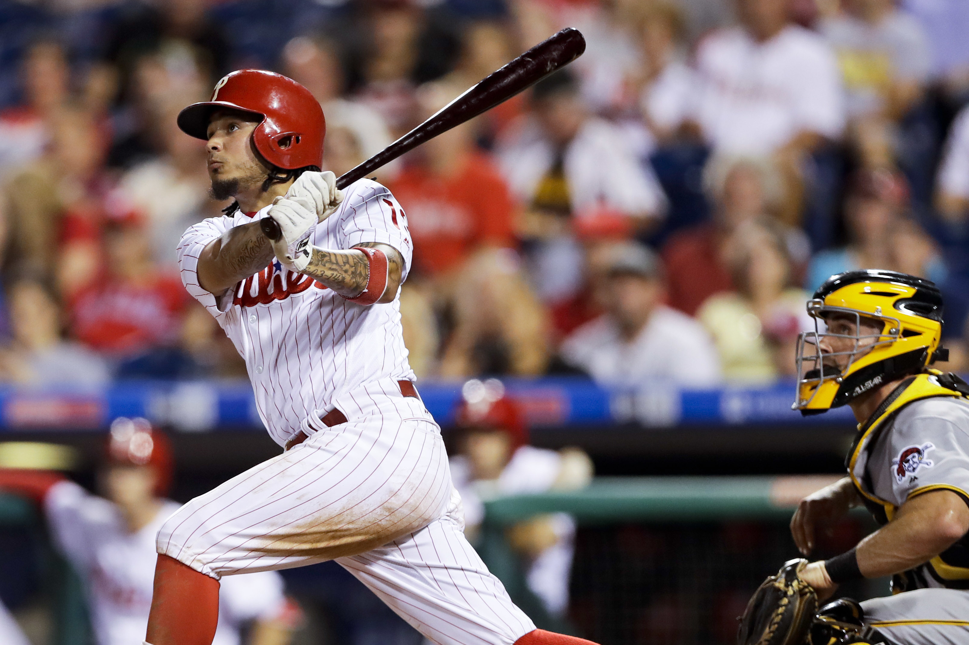 Philadelphia Phillies' Freddy Galvis follows through after hitting a two-run home run off Pittsburgh Pirates starting pitcher Steven Brault during the second inning of a baseball game, Wednesday, Sept. 14, 2016, in Philadelphia. At right is catcher Eric F