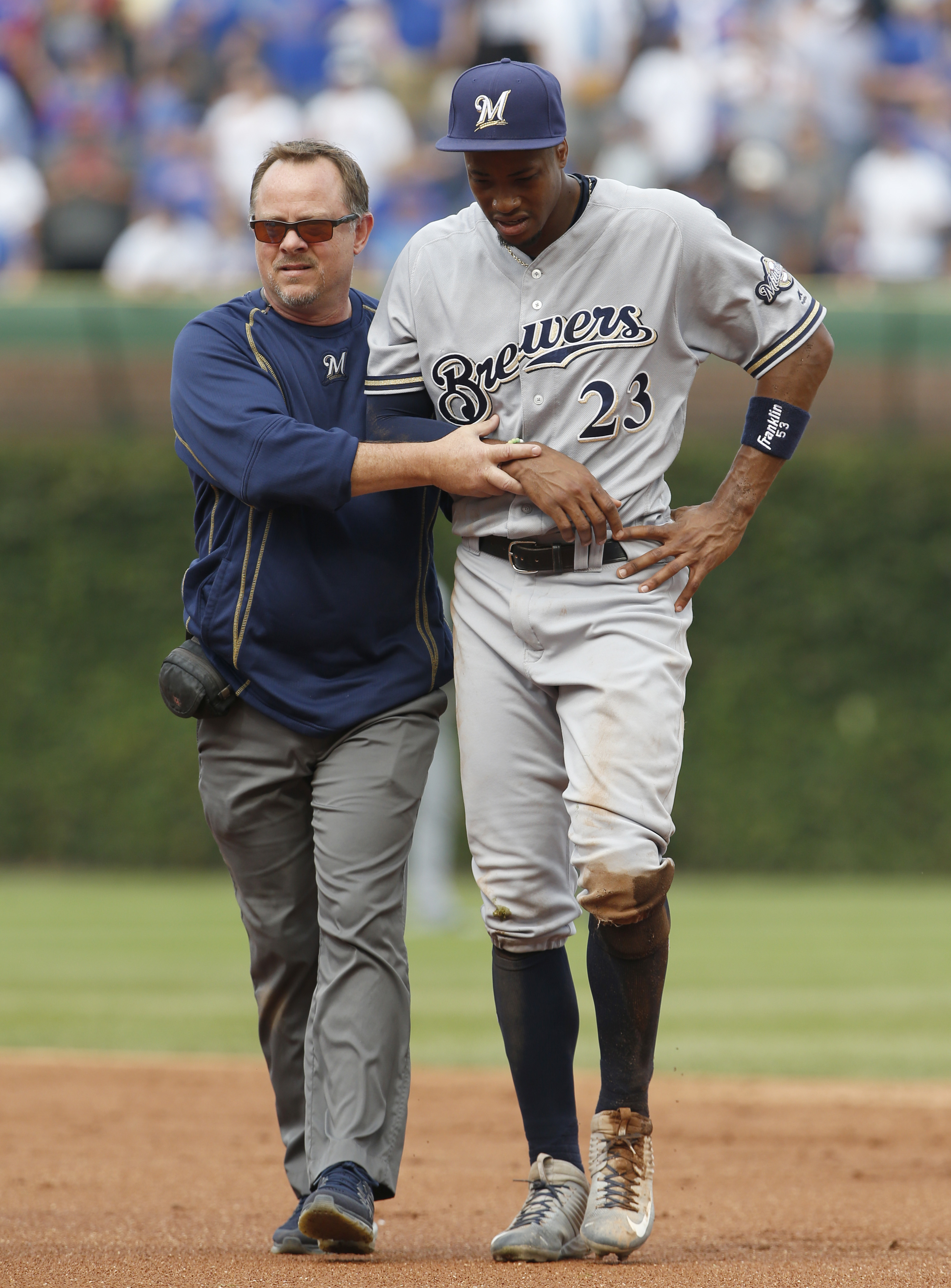 Milwaukee Brewers center fielder Keon Broxton, right, is helped off the field by the trainer after he crashed into the outfield wall during the third inning of a baseball game against the Chicago Cubs, Friday, Sept. 16, 2016, in Chicago. (AP Photo/Nam Y.