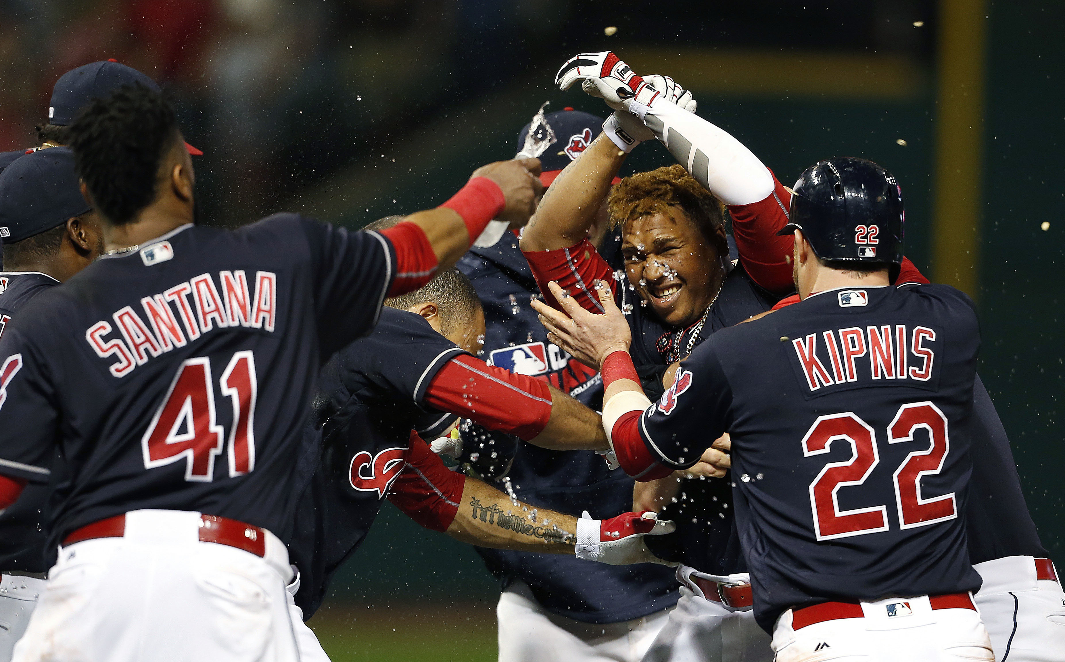 Cleveland Indians' Jose Ramirez, second from right, is mobbed by teammates after hitting a game winning single off Detroit Tigers relief pitcher Justin Wilson during the tenth inning of a baseball game Saturday, Sept. 17, 2016, in Cleveland. The Indians w
