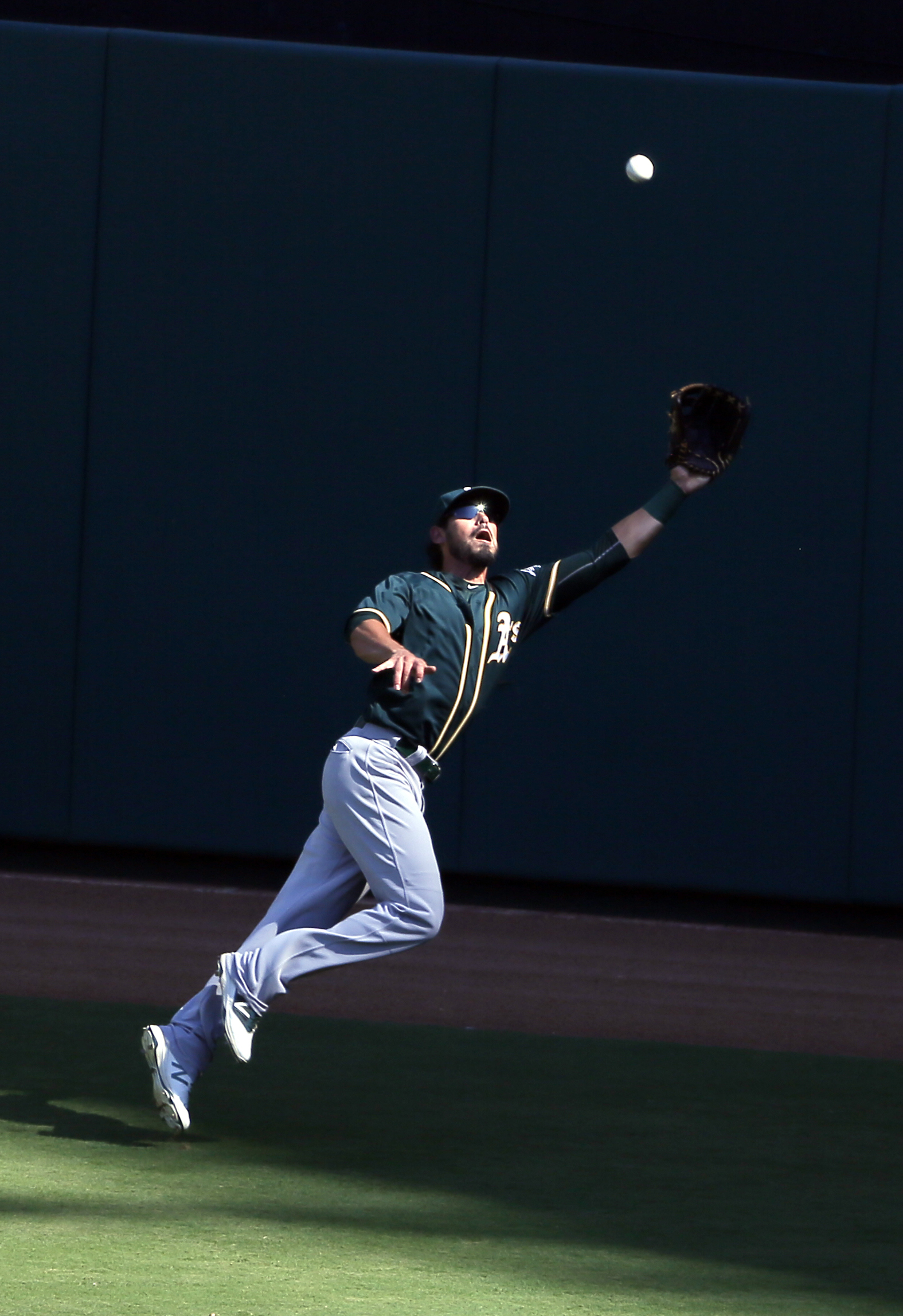 Oakland Athletics right fielder Brett Eibner reaches up before laying out to catch a fly out by Texas Rangers' Adrian Beltre in the fifth inning of a baseball game, Sunday, Sept. 18, 2016, in Arlington, Texas. (AP Photo/Tony Gutierrez)