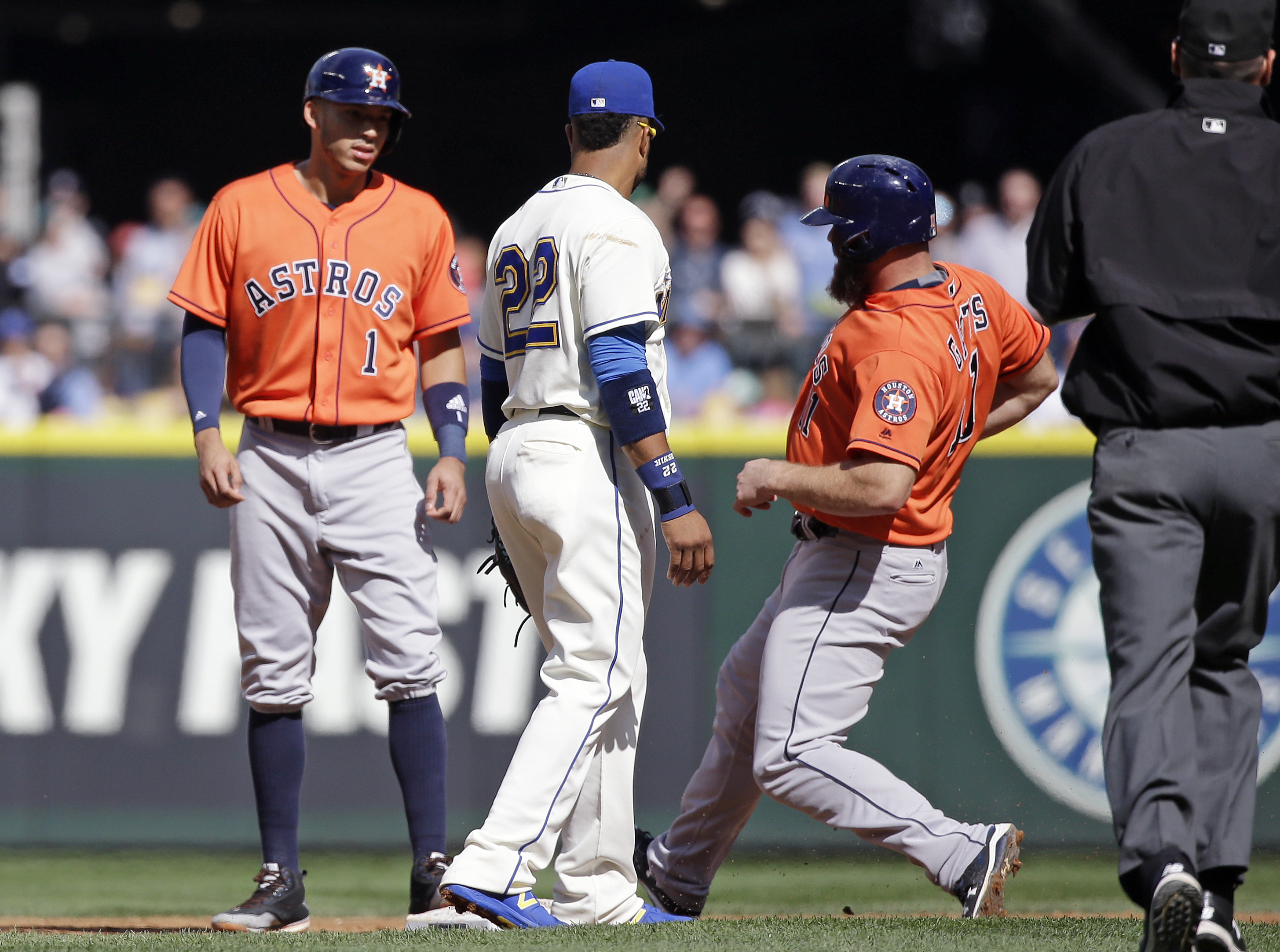 Seattle Mariners second baseman Robinson Cano (22) looks on as Houston Astros' Evan Gattis, right, arrives at second base, already occupied by Carlos Correa, in the second inning of a baseball game Sunday, Sept. 18, 2016, in Seattle. Gattis was tagged out