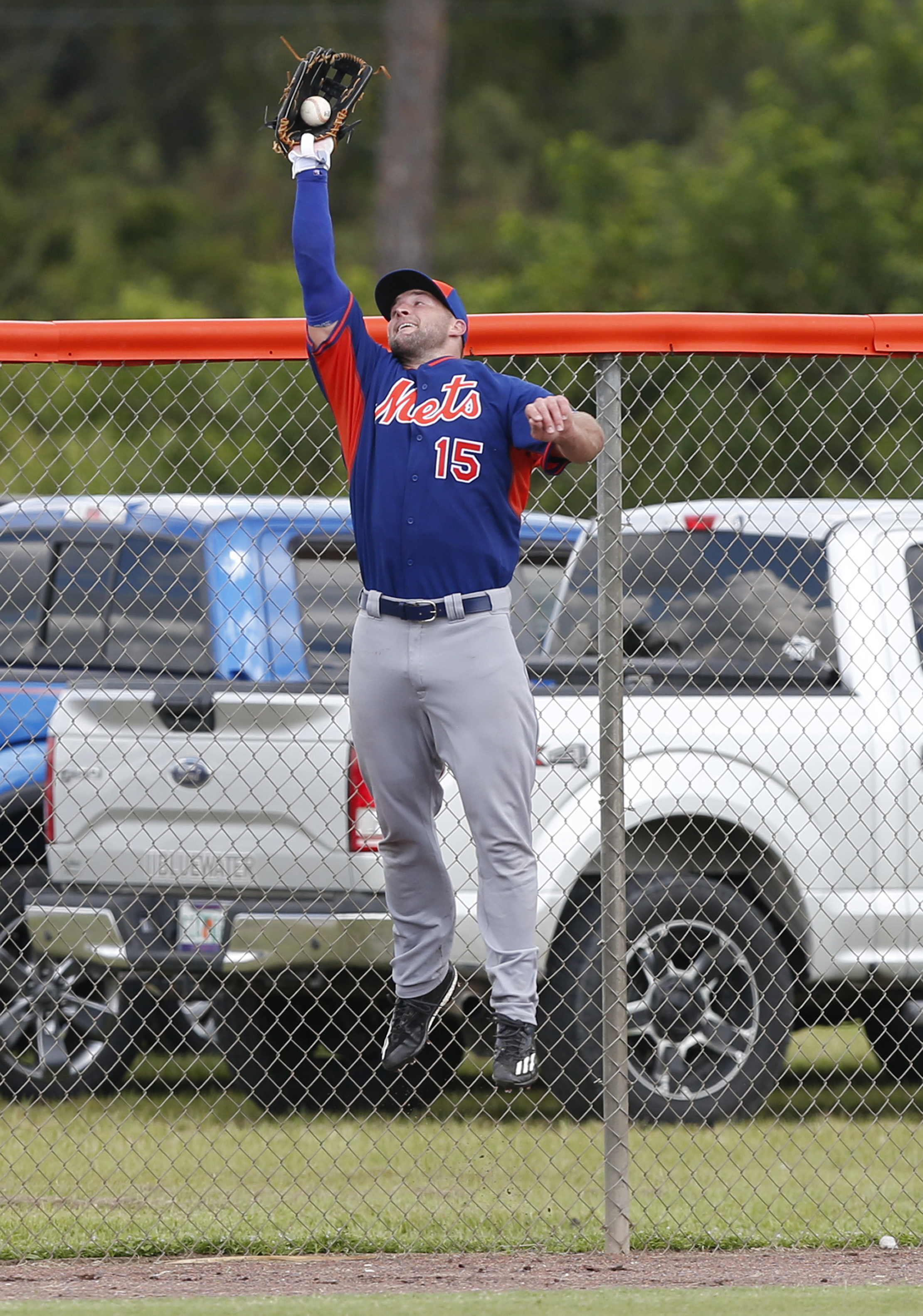 Tim Tebow catches a ball at the fence during a drill at the New York Mets' complex, Monday, Sept. 19, 2016, in Port St. Lucie, Fla. The 2007 Heisman Trophy winner and former NFL quarterback got to the complex early Monday, and started his first workout as