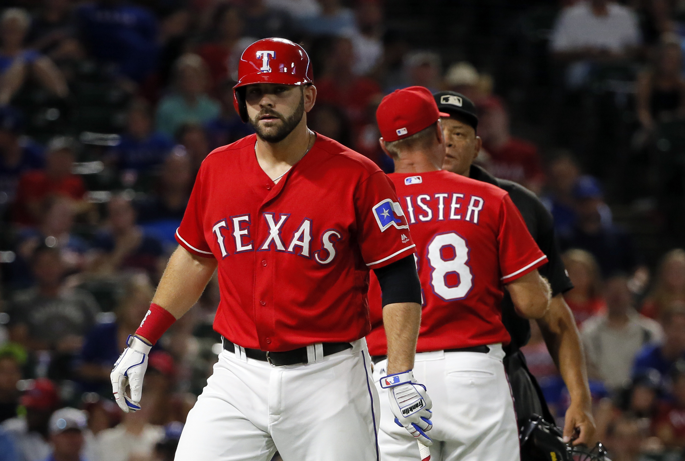 Texas Rangers' Mitch Moreland walks to the dugout after being ejected from the game by umpire Kerwin Danley, rear, who argues with manager Jeff Banister (28) in the fourth inning of a baseball game, Monday, Sept. 19, 2016, in Arlington, Texas. (AP Photo/T