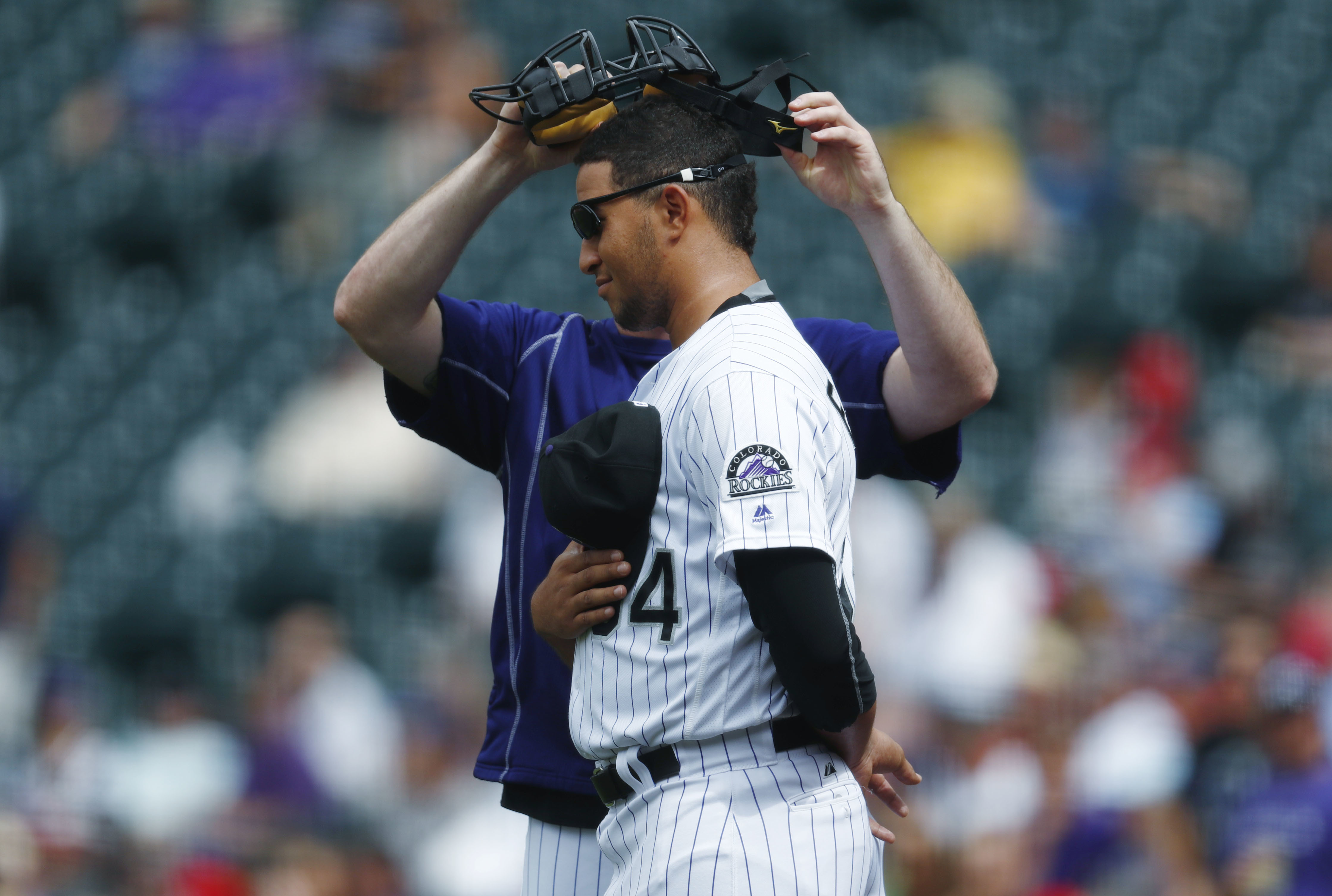 Colorado Rockies relief pitcher Carlos Estevez is fitted for a catcher's mask by relief pitcher Boone Logan as Estevez takes part in a stand off against St. Louis Cardinals right fielder Jose Martinez after the teams dispersed from the warning track follo