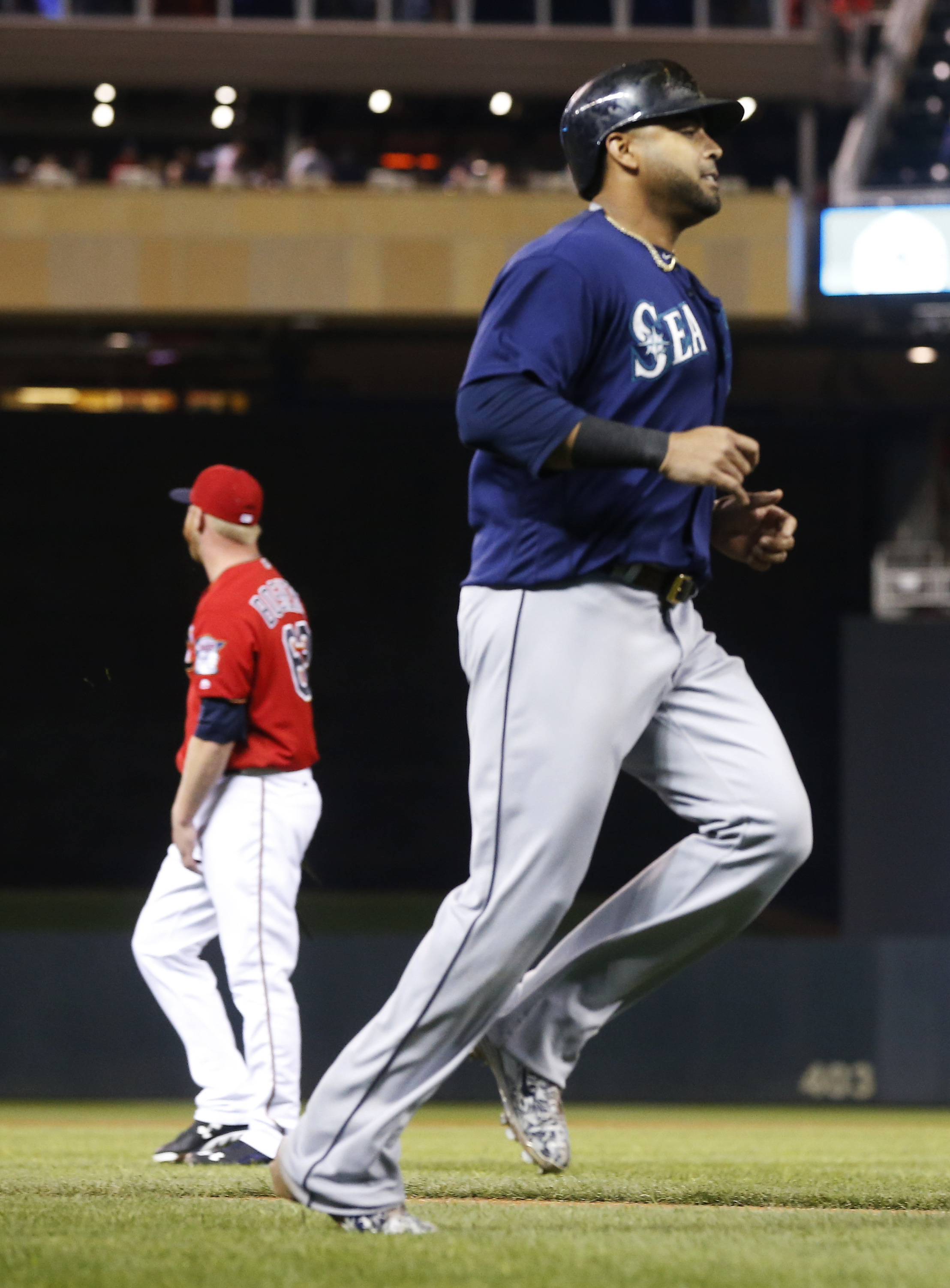 Seattle Mariners' Nelson Cruz jogs home on an RBI double by Kyle Seager off Minnesota Twins pitcher Buddy Boshers, left, during the seventh inning of a baseball game Friday, Sept. 23, 2016, in Minneapolis. (AP Photo/Jim Mone)