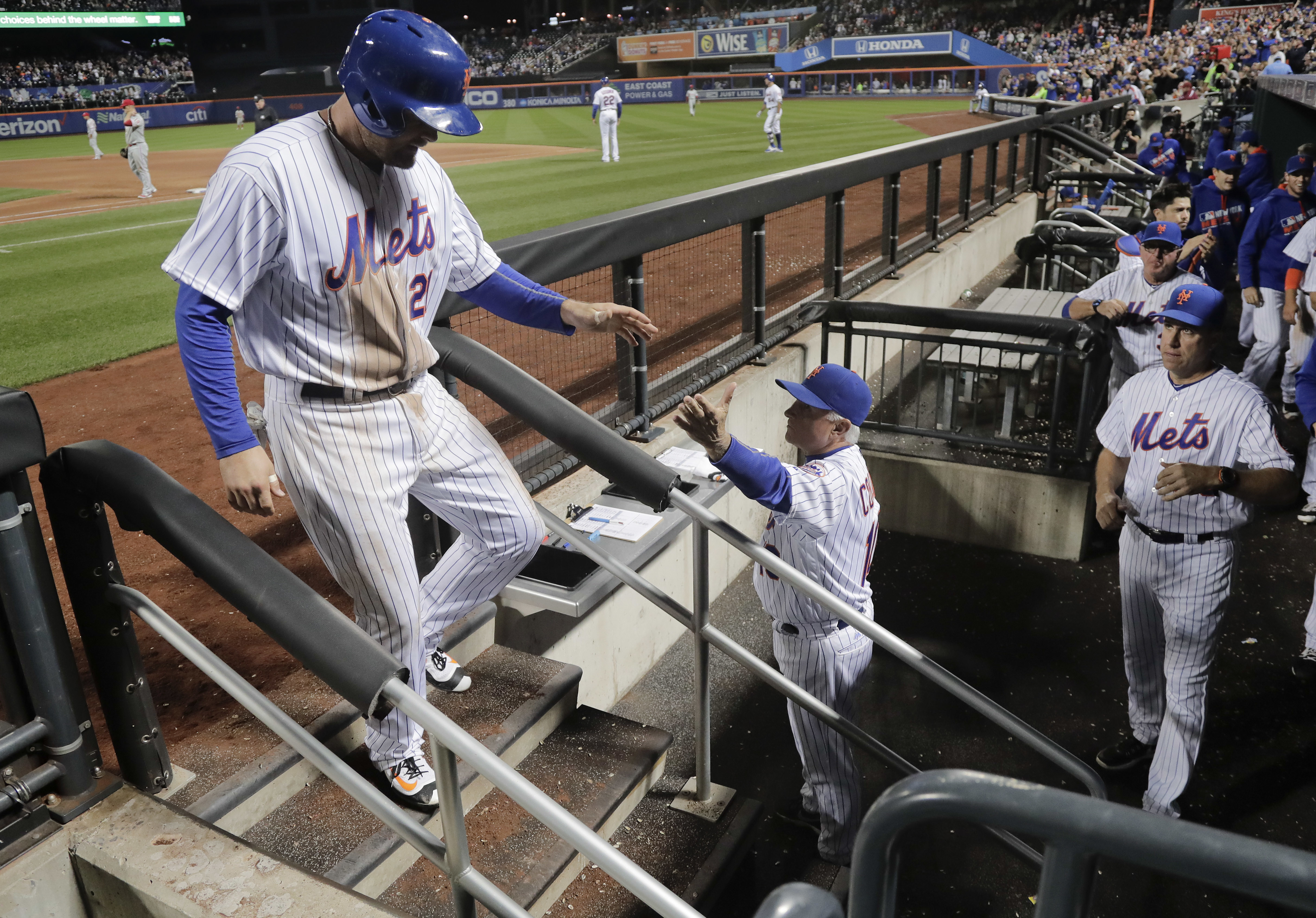 New York Mets' Lucas Duda (21) is greeted in the dugout after scoring during the sixth inning of a baseball game against the Philadelphia Phillies, Saturday, Sept. 24, 2016, in New York. (AP Photo/Julie Jacobson)