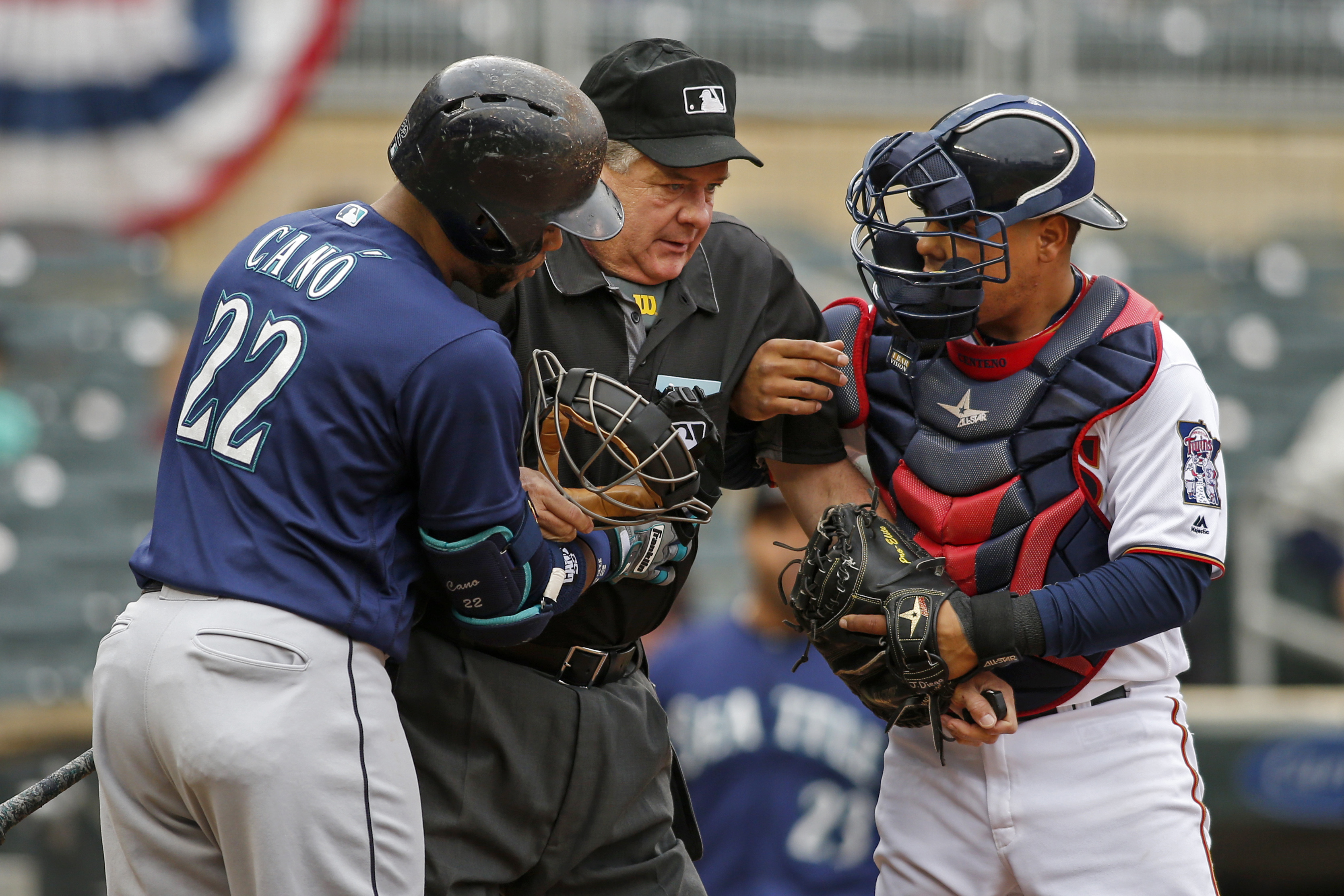 Seattle Mariners' Robinson Cano, left, and Minnesota Twins catcher Juan Centeno, right, hold up umpire Jerry Layne  who was hit by a foul ball in the first inning of a baseball game Sunday, Sept. 25, 2016, in Minneapolis. Layne left the game. (AP Photo/Br