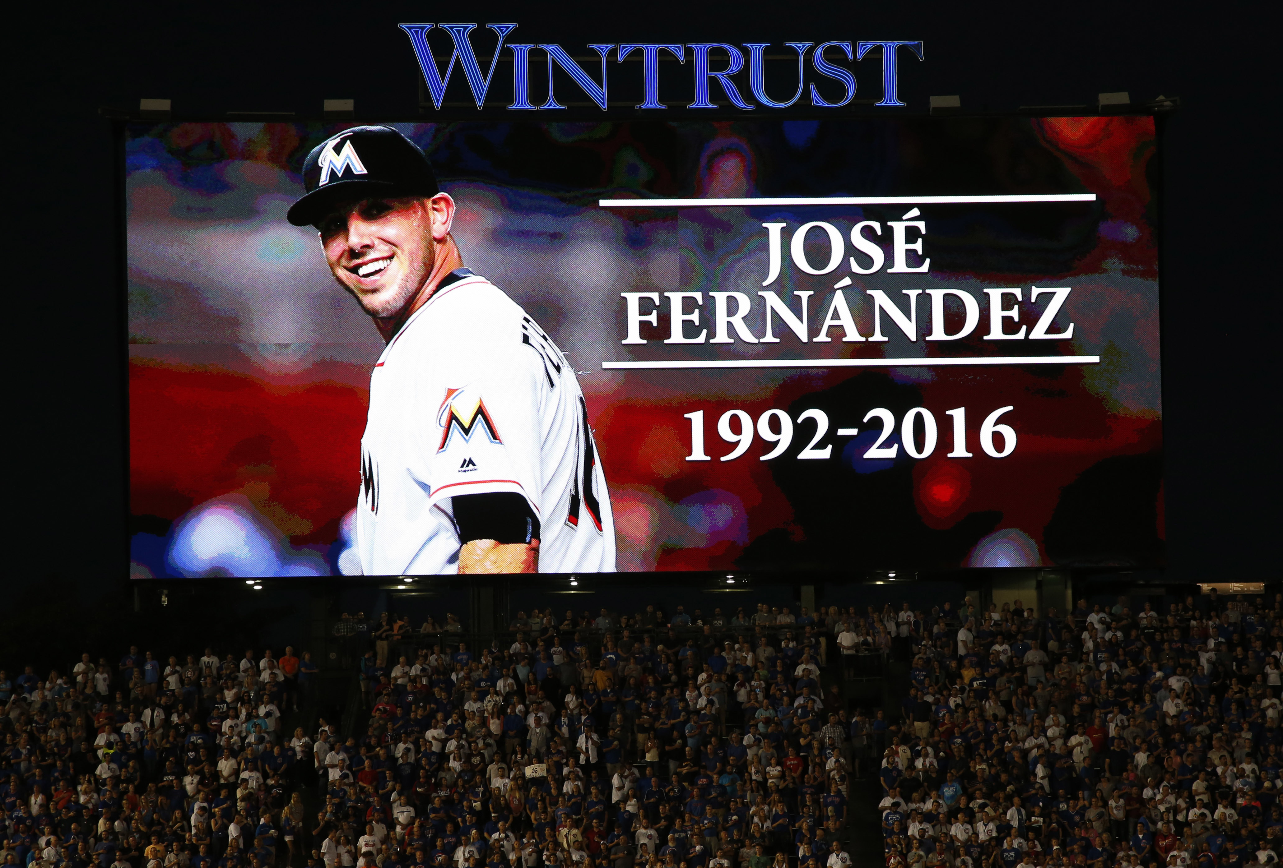 Baseball fans stand for a minute of silence for Miami Marlins pitcher Jose Fernandez, who was killed early Sunday, Sept. 25, 2016 in a boating accident in Miami, before a baseball game between the St. Louis Cardinals and the Chicago Cubs Sunday, Sept. 25,