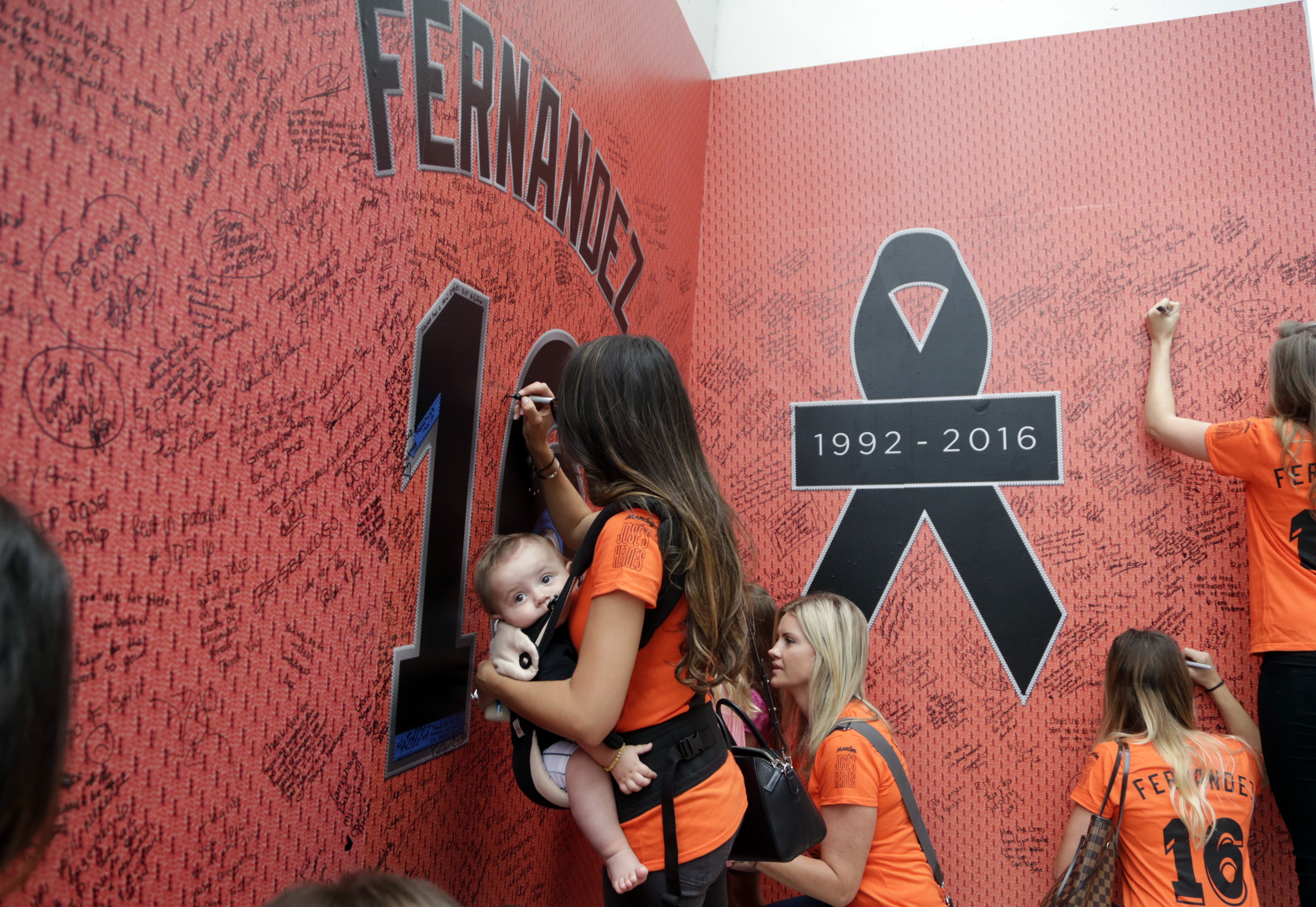 Fans sign a wall at a makeshift memorial for Miami Marlins pitcher Jose Fernandez before a baseball game between the Miami Marlins and the New York Mets , Monday, Sept. 26, 2016, in Miami. Fernandez died in a boating accident early Sunday. (AP Photo/Lynne