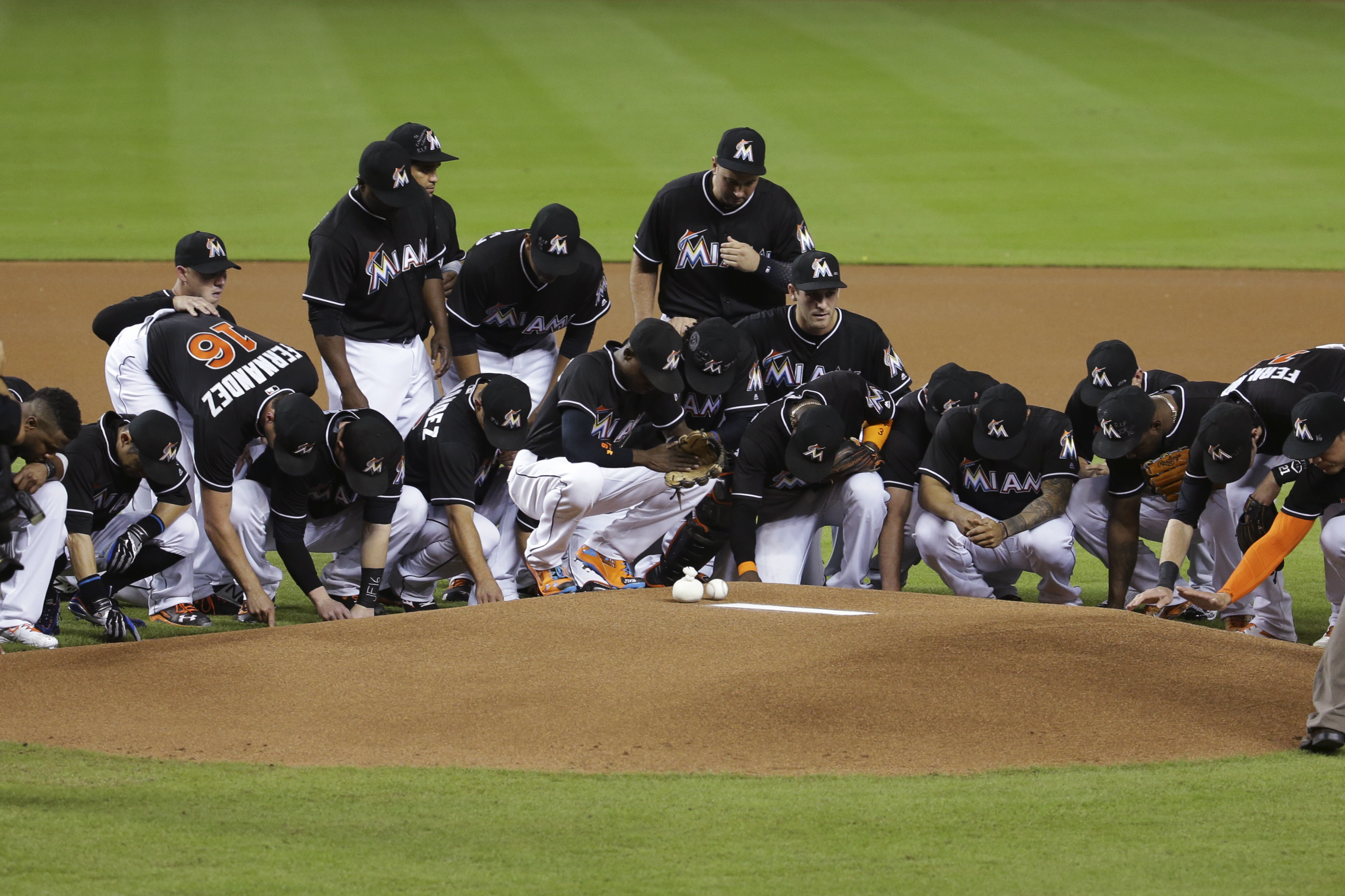Miami Marlins players wearing a jersey in honor of pitcher Jose Fernandez (16) gather around the pitching mound before a baseball game against the New York Mets, Monday, Sept. 26, 2016, in Miami. Fernandez died in a boating accident Sunday. (AP Photo/Lynn