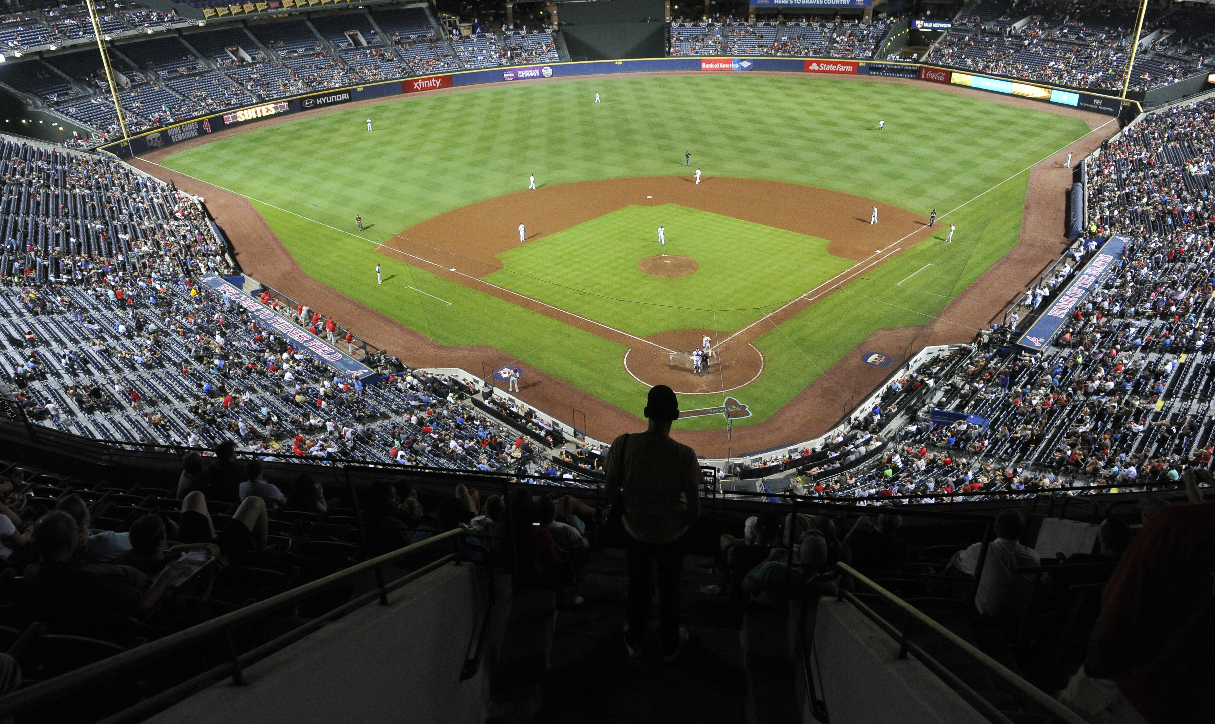 A fan watches the ninth inning of the Atlanta Braves' baseball game against the Philadelphia Phillies at Turner Field, Wednesday, Sept. 28, 2016, in Atlanta. Atlanta won 12-2. The Braves are scheduled to move to a new stadium next season.  (AP Photo/John