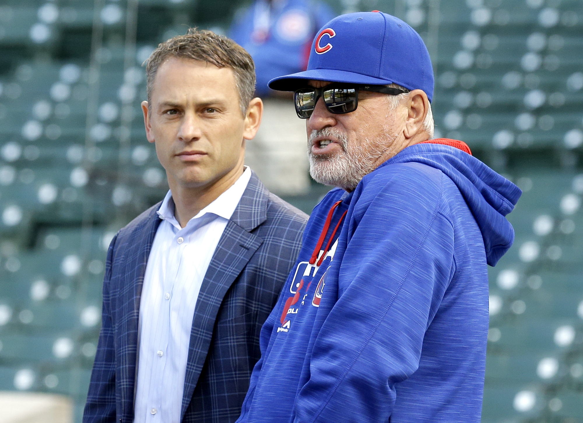 Chicago Cubs manager Joe Maddon, right, talks with general manager Jed Hoyer at the Wrigley Field before the start of an opening day baseball game between the Cincinnati Reds and the Chicago Cubs on Monday, April 11, 2016, in Chicago. (AP Photo/Nam Y. Huh