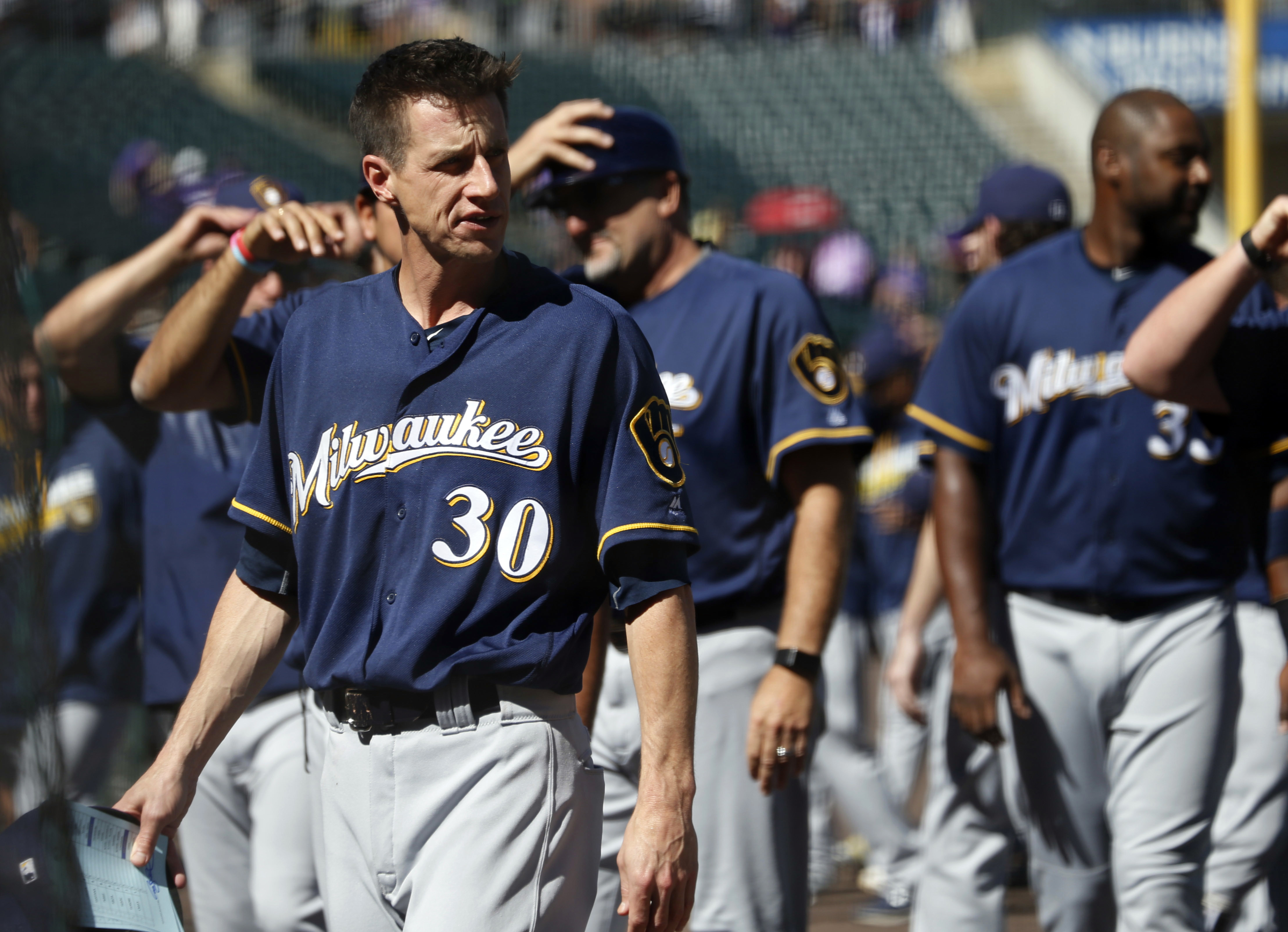 Milwaukee Brewers manager Craig Counsell leads his players back to the dugout after the playing of the national anthem before facing the Colorado Rockies in a baseball game Sunday, Oct. 2, 2016, in Denver. (AP Photo/David Zalubowski)