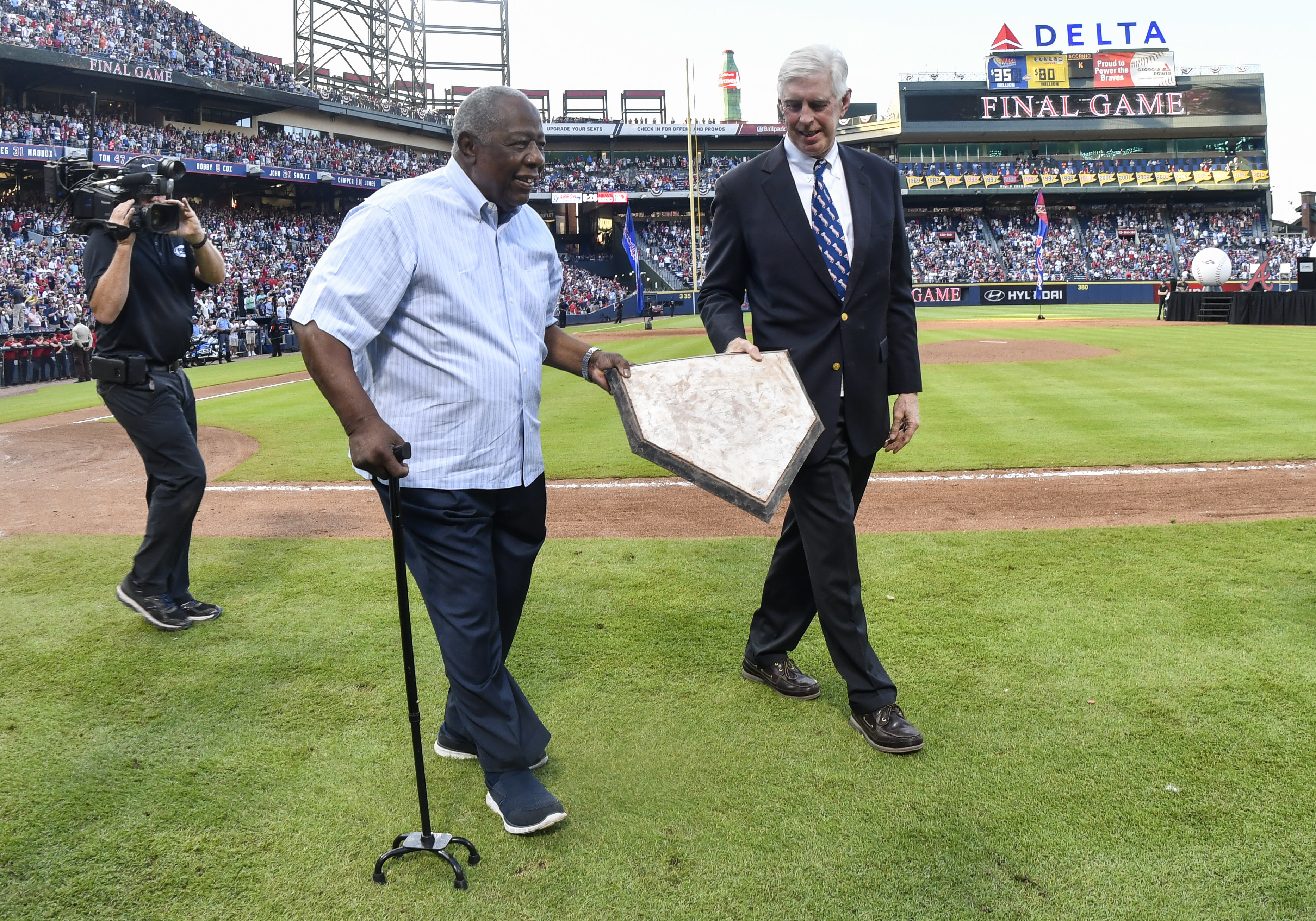 Former Atlanta Braves player and home run record holder Hank Aaron and Braves Chairman Terry McGuirk, right, take home plate, which was taken up from Turner Field, to a van that will take it to SunTrust Park after the baseball game against the Detroit Tig