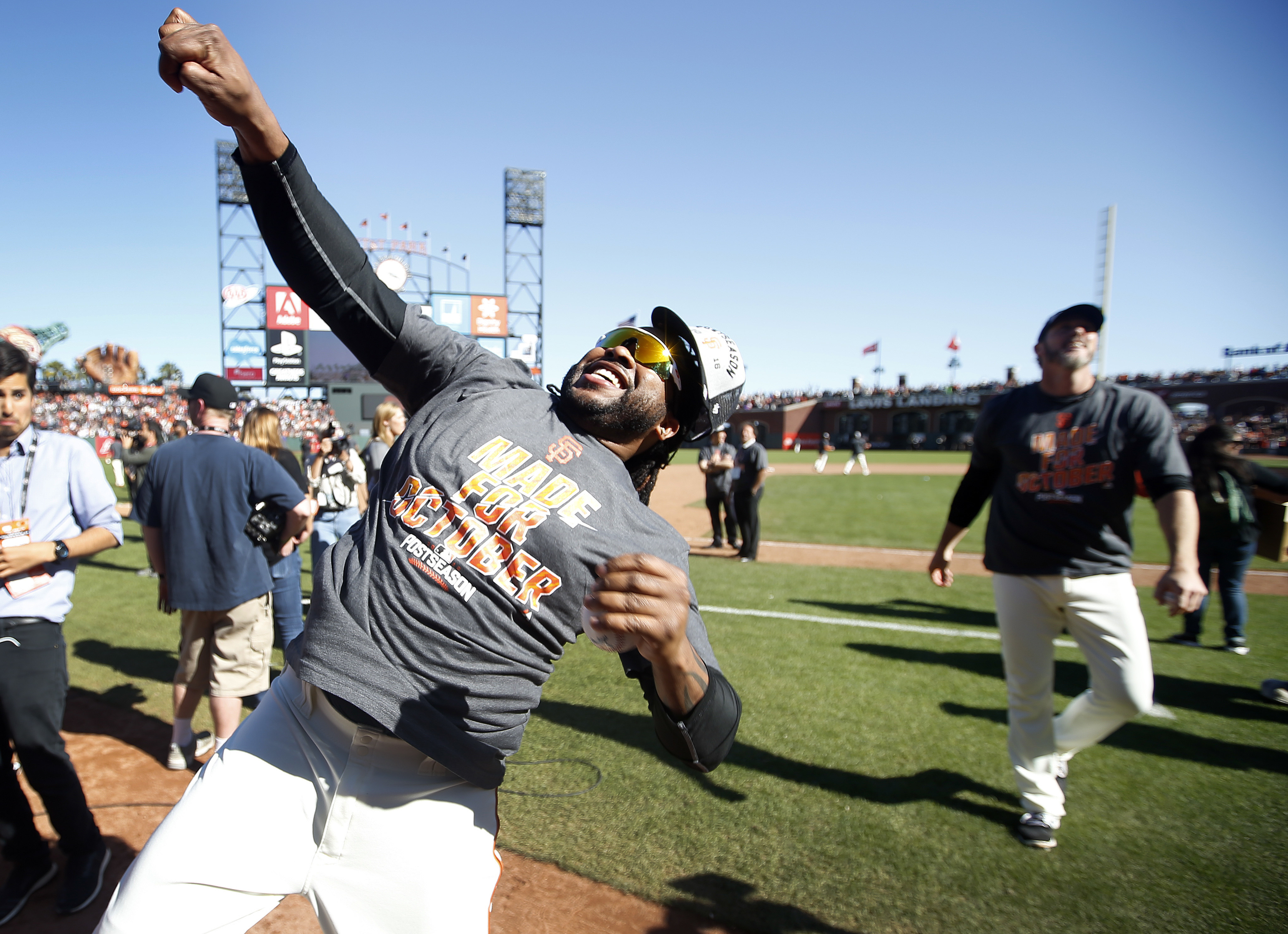 San Francisco Giants' Johnny Cueto, throws a ball into the crowd during a celebration on the field after clinching NL second-place wild card spot following their win over the Los Angeles Dodgers in a baseball game in San Francisco, Sunday, Oct. 2, 2016. (