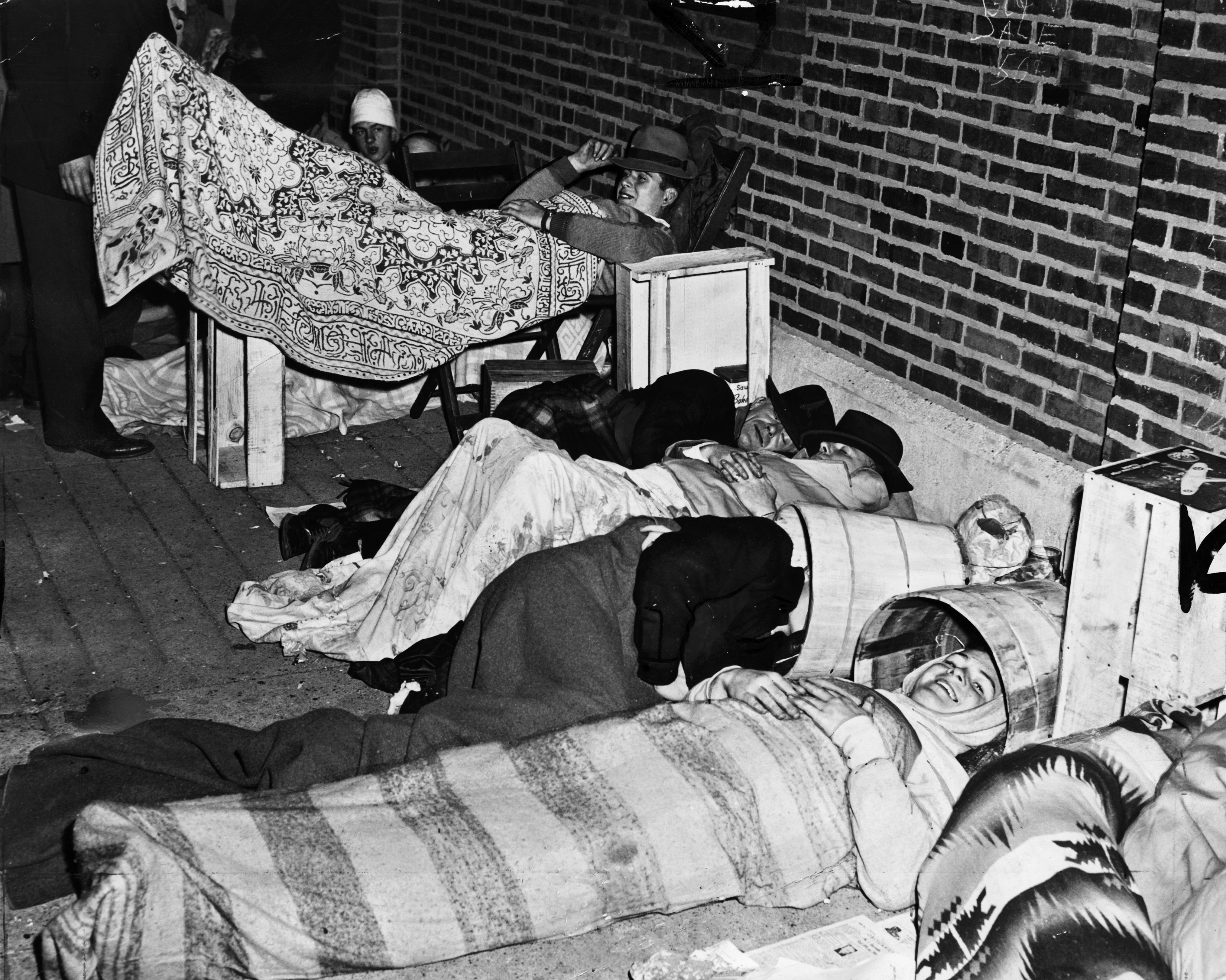 In this 1945 photo, fans rest as they camp out overnight for bleacher tickets for the World Series baseball games between the Chicago White Sox and the Chicago Cubs at Wrigley Field in Chicago. Some fans used tubs and baskets to keep the rain off their fa