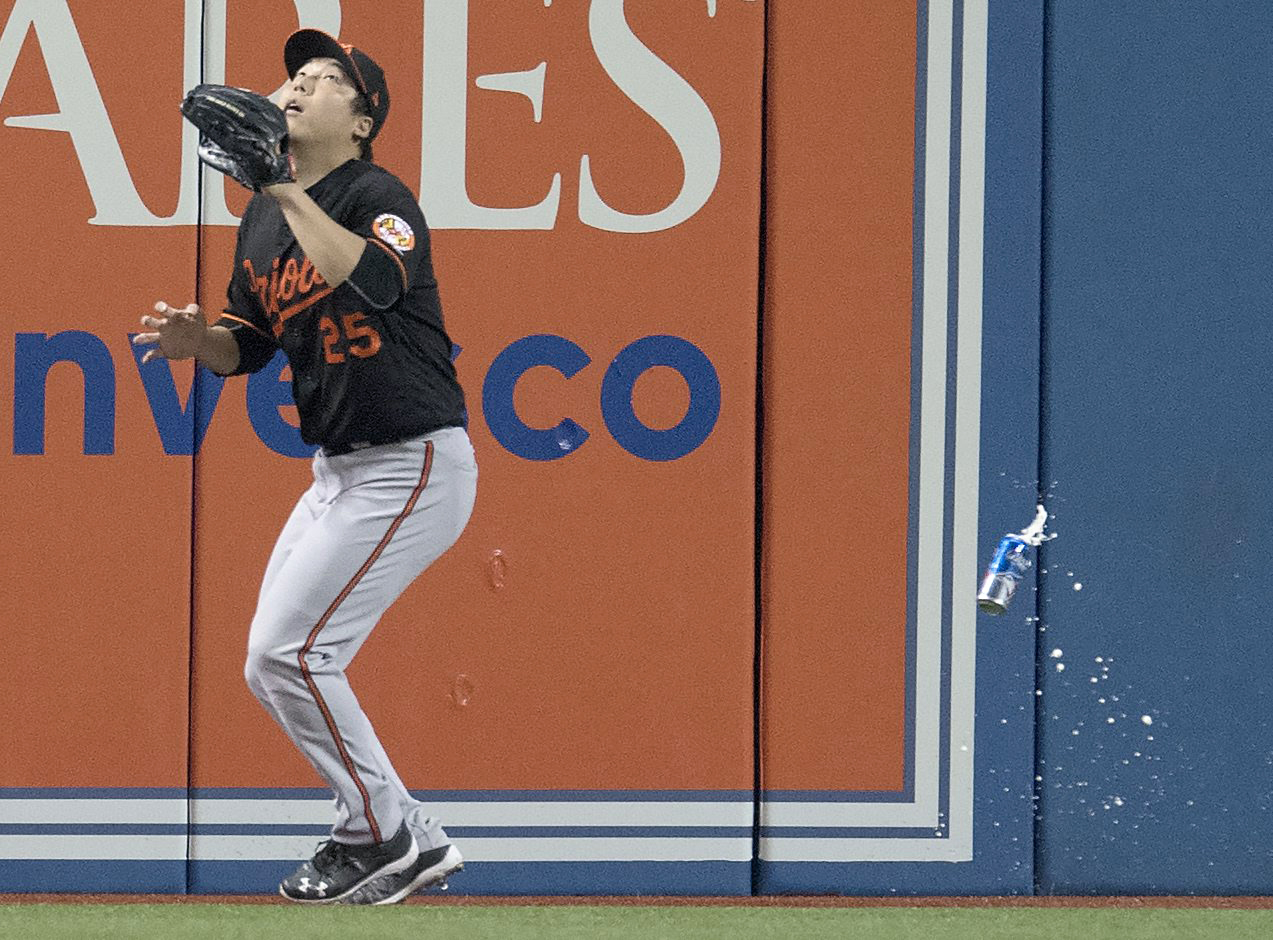 Baltimore Orioles' Hyun Soo Kim gets under a fly ball as a can falls past him during the seventh inning of an American League wild-card baseball game against the Toronto Blue Jays in Toronto, Tuesday, Oct. 4, 2016. (Mark Blinch/The Canadian Press via AP)