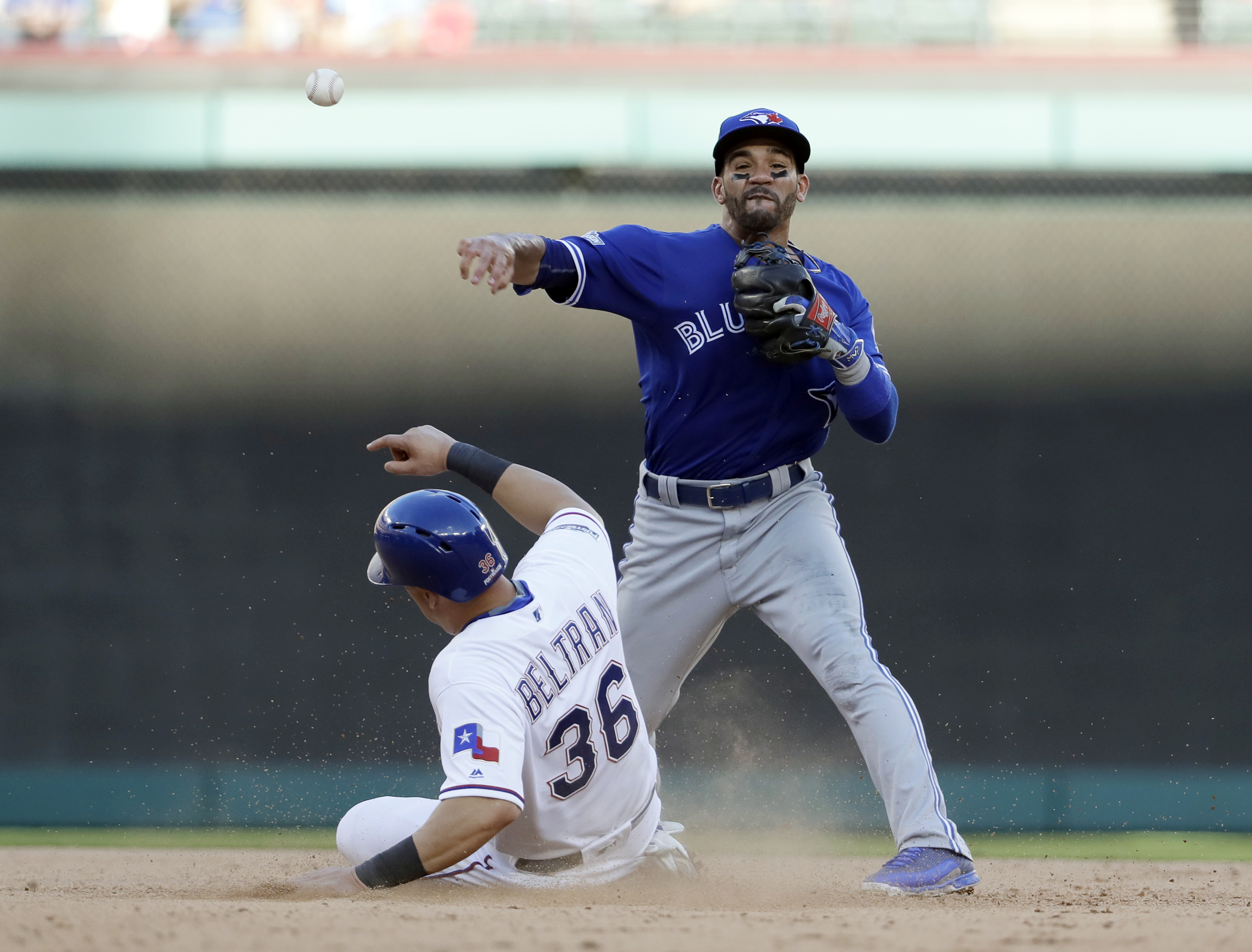 Toronto Blue Jays second baseman Devon Travis throws to first for the double play after forcing out Texas Rangers' Carlos Beltran during the seventh inning of Game 1 baseball's American League Division Series, Thursday, Oct. 6, 2016, in Arlington, Texas.