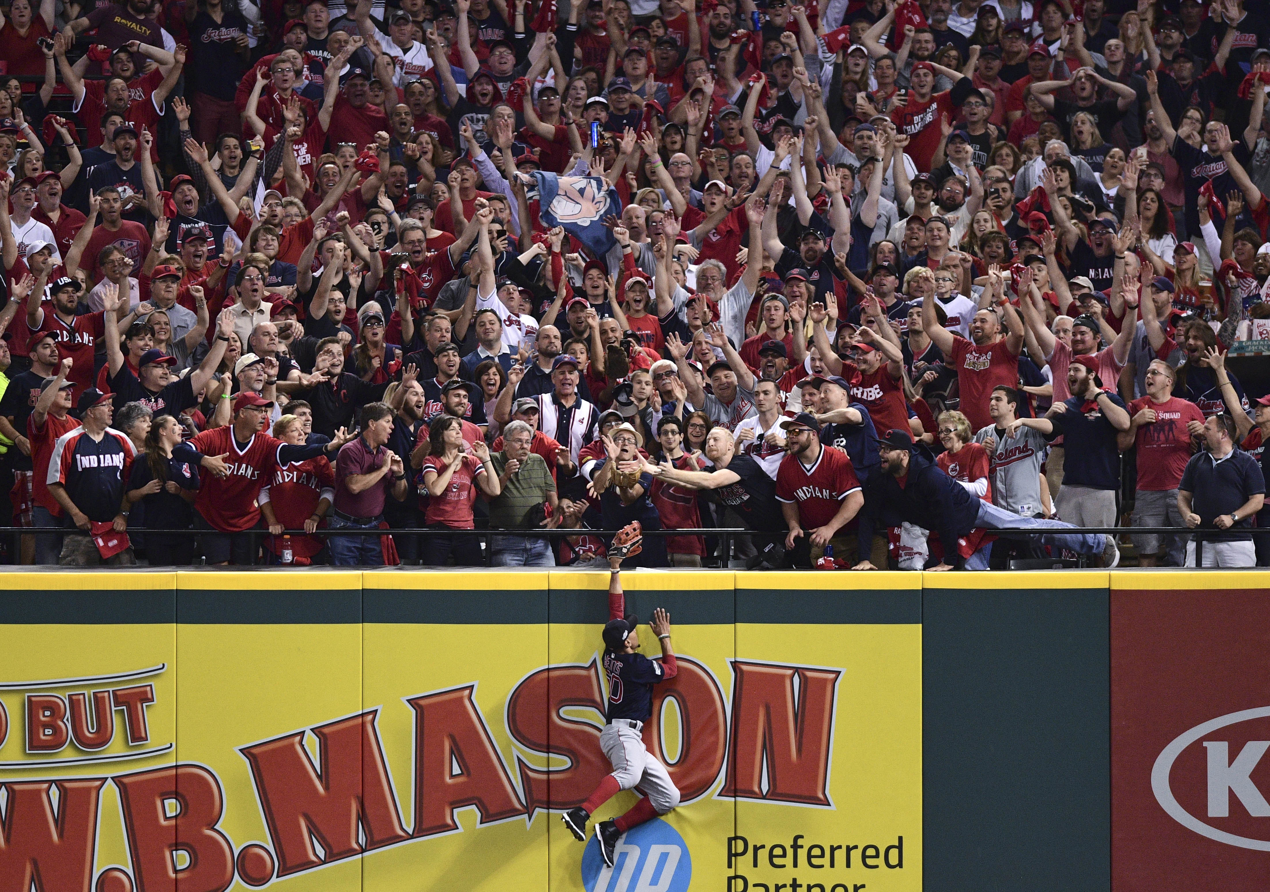 Fans try to for a Cleveland Indians' Francisco Lindor home run ball as Boston Red Sox right fielder Mookie Betts attempts to make a catch in the third inning as during Game 1 of baseball's American League Division Series, Thursday, Oct. 6, 2016, in Clevel