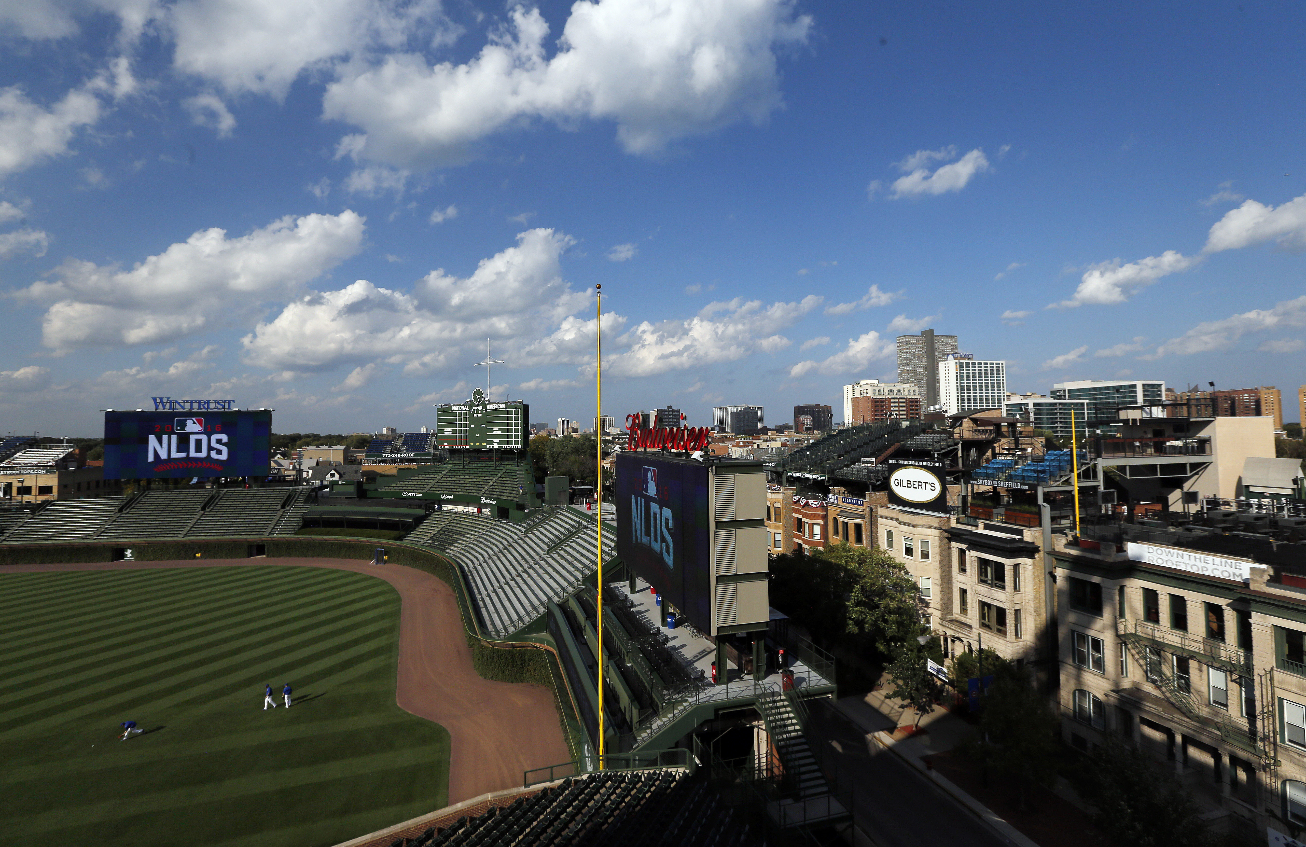 The Wrigleyville neighborhood stands beyond right field as Chicago Cubs players prepare for Game 1 of the National League Division Series against the San Francisco Giants, Wednesday, Oct. 5, 2016, in Chicago. Living near the workplace is one of the unique