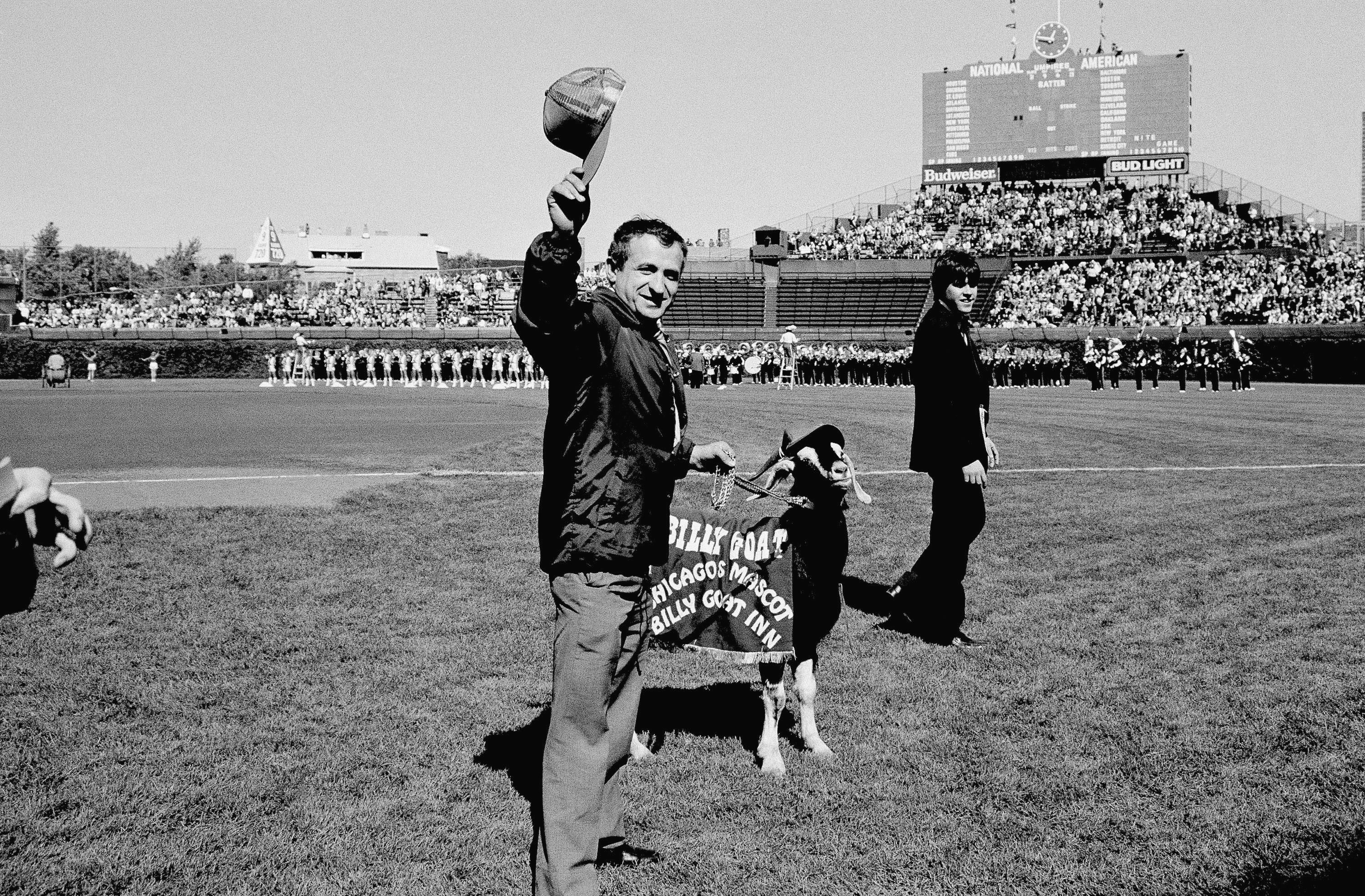FILE - In this Oct. 2, 1984 file photo, Sam Sianis, owner of the Billy Goat Tavern in Chicago, acknowledges the crowd along with his goat prior to a National League playoff game between the San Diego Padres and the Cubs in Chicago. Cubs fans Erik Williams