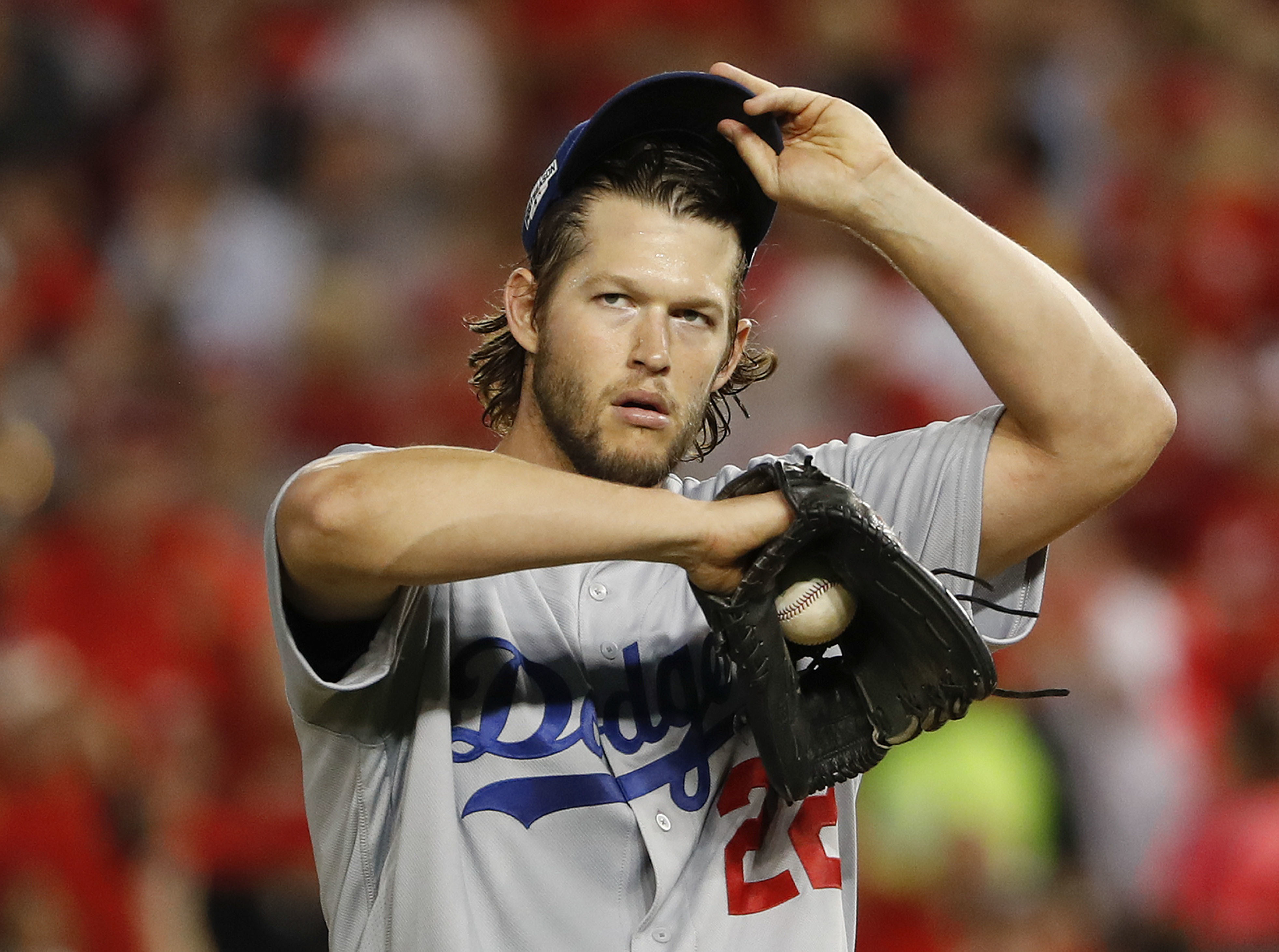 Los Angeles Dodgers starting pitcher Clayton Kershaw adjusts his cap after allowing a double by Washington Nationals' Bryce Harper during the third inning in Game 1 of baseball's National League Division Series at Nationals Park, Friday, Oct. 7, 2016, in