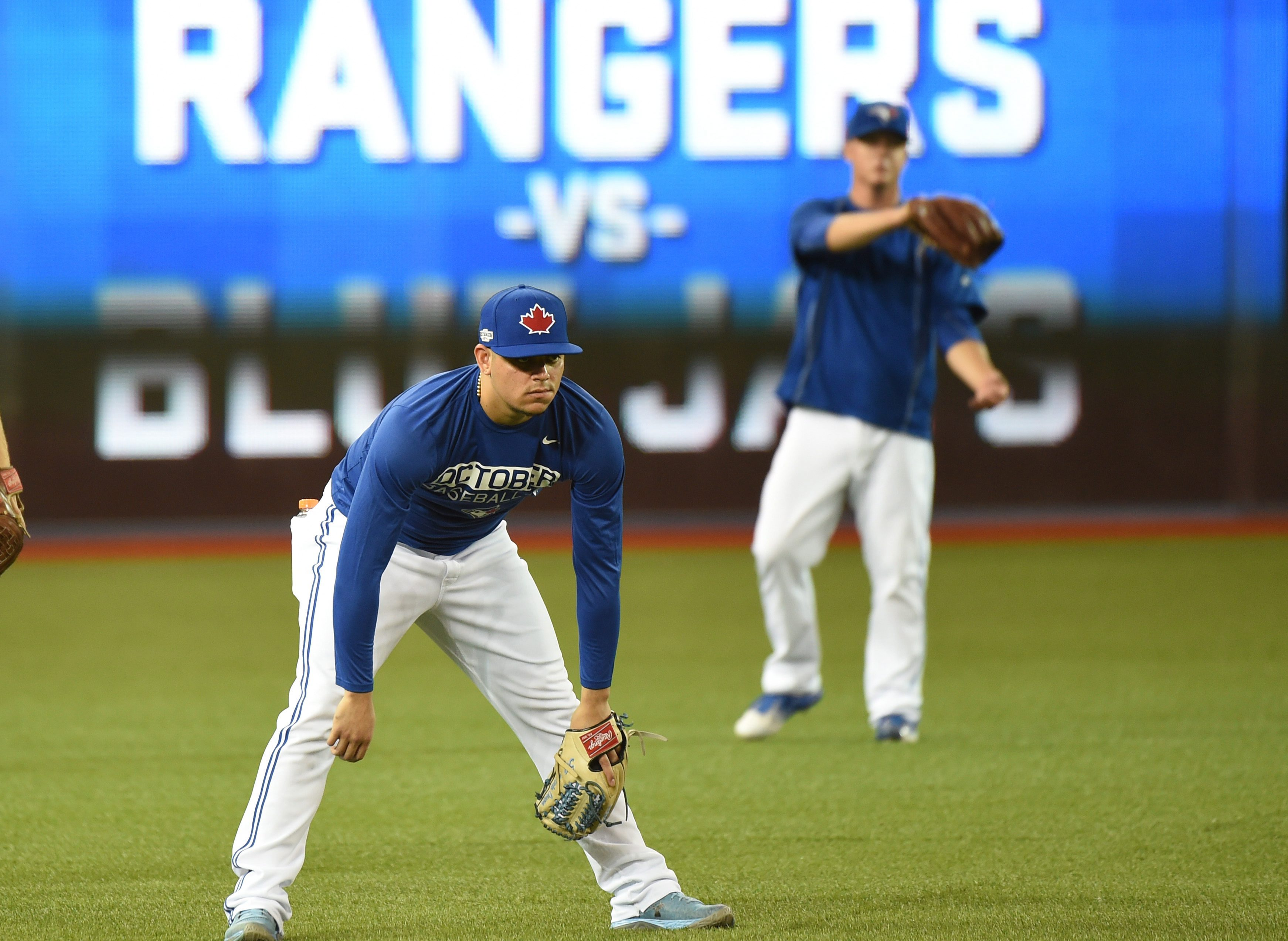 Toronto Blue Jays relief pitcher Roberto Osuna, left, warms up during a baseball workout ahead of Game 3 in the American League Division Series  in Toronto on Saturday, Oct. 8, 2016. (Jon Blacker/The Canadian Press via AP)