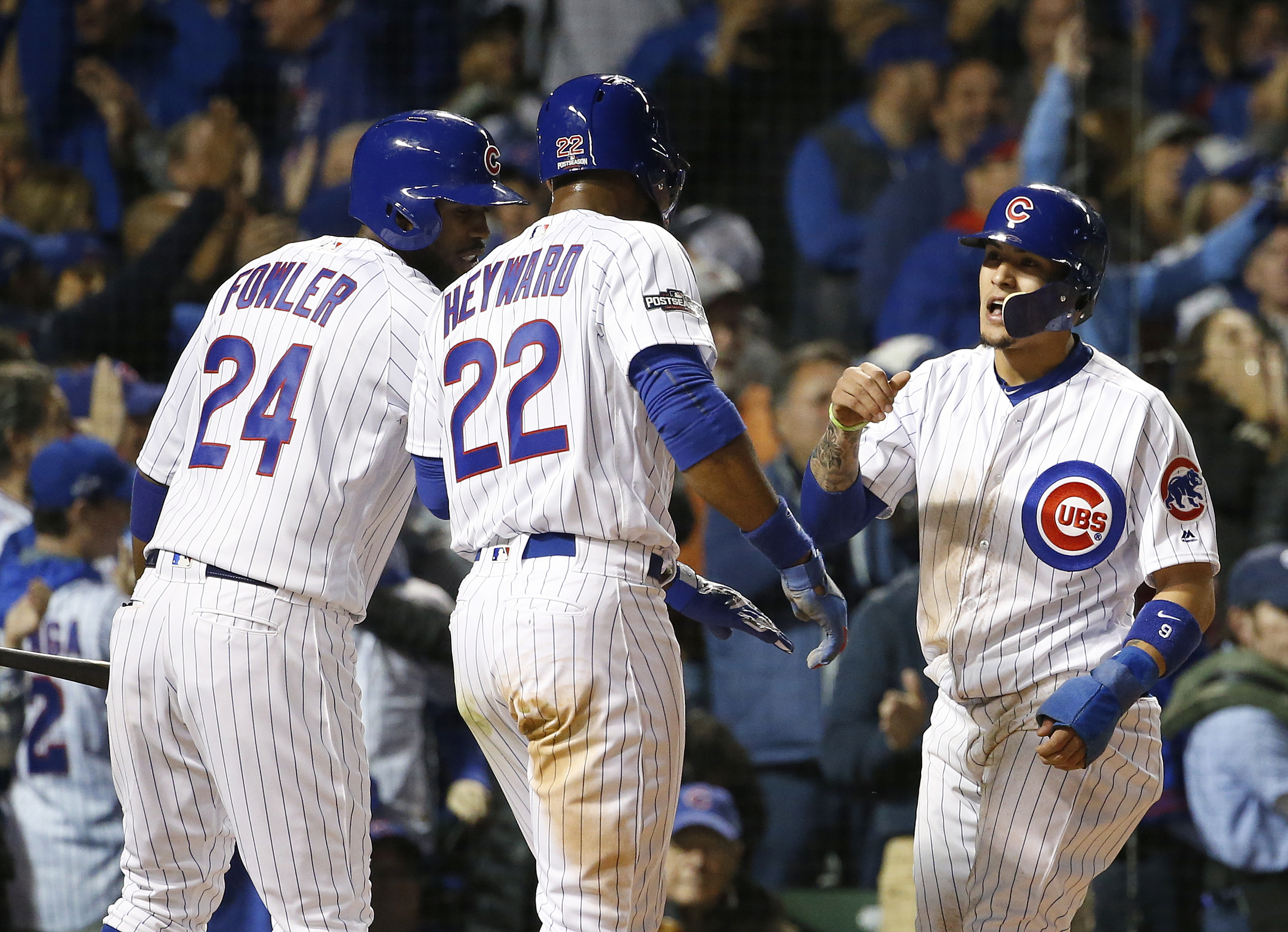 Chicago Cubs' Javier Baez celebrates with Dexter Fowler (24) and Jason Heyward (22) after sliding safely into home after a single by Kyle Hendricks  in the second inning of Game 2 of baseball's National League Division Series, Saturday, Oct. 8, 2016, in C