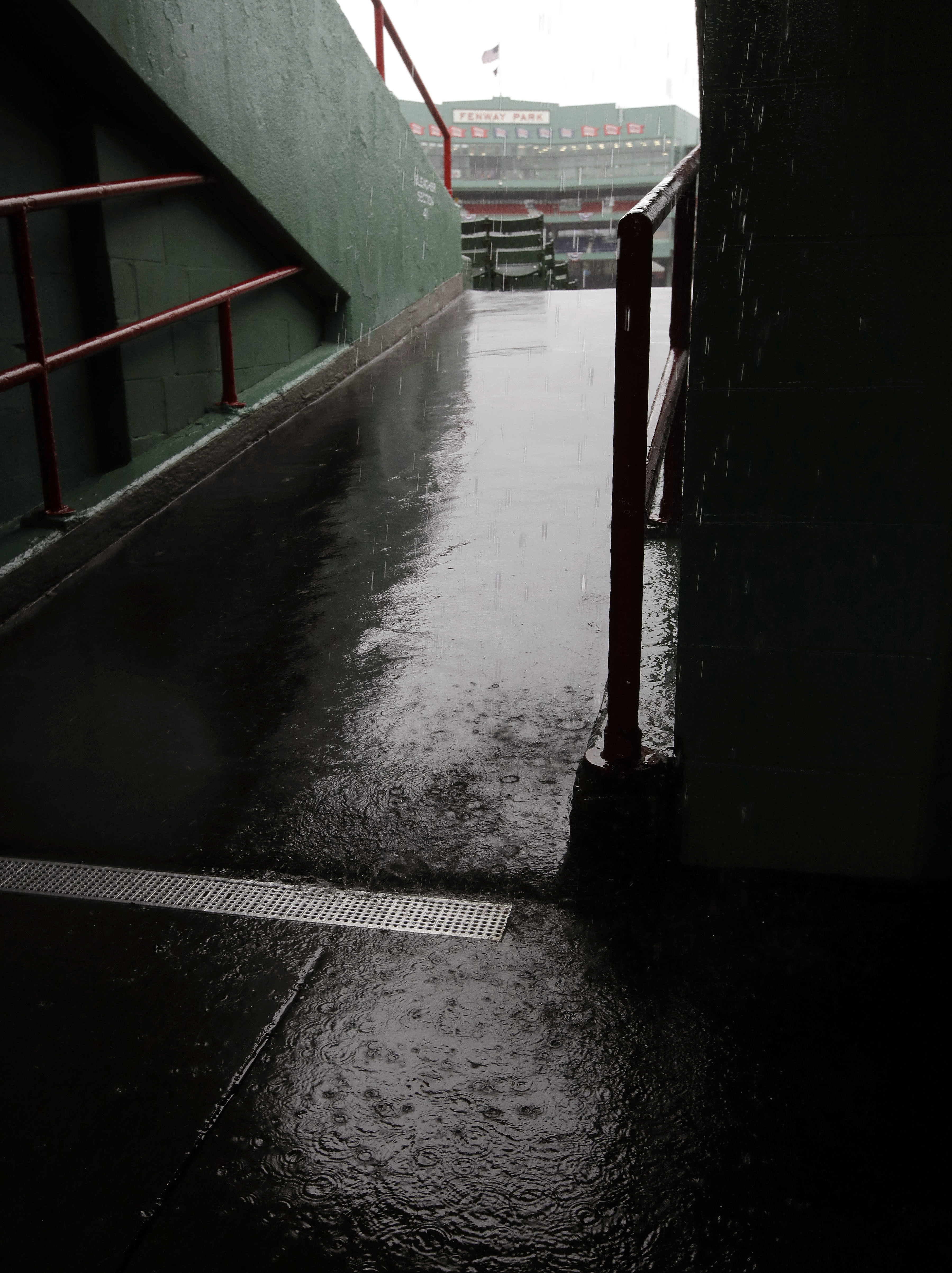 Rain drops splash in a puddle in an outfield concourse at Fenway Park during steady rain before Game 3 of baseball's American League Division Series between the Cleveland Indians and the Boston Red Sox, Sunday, Oct. 9, 2016, in Boston. (AP Photo/Charles K