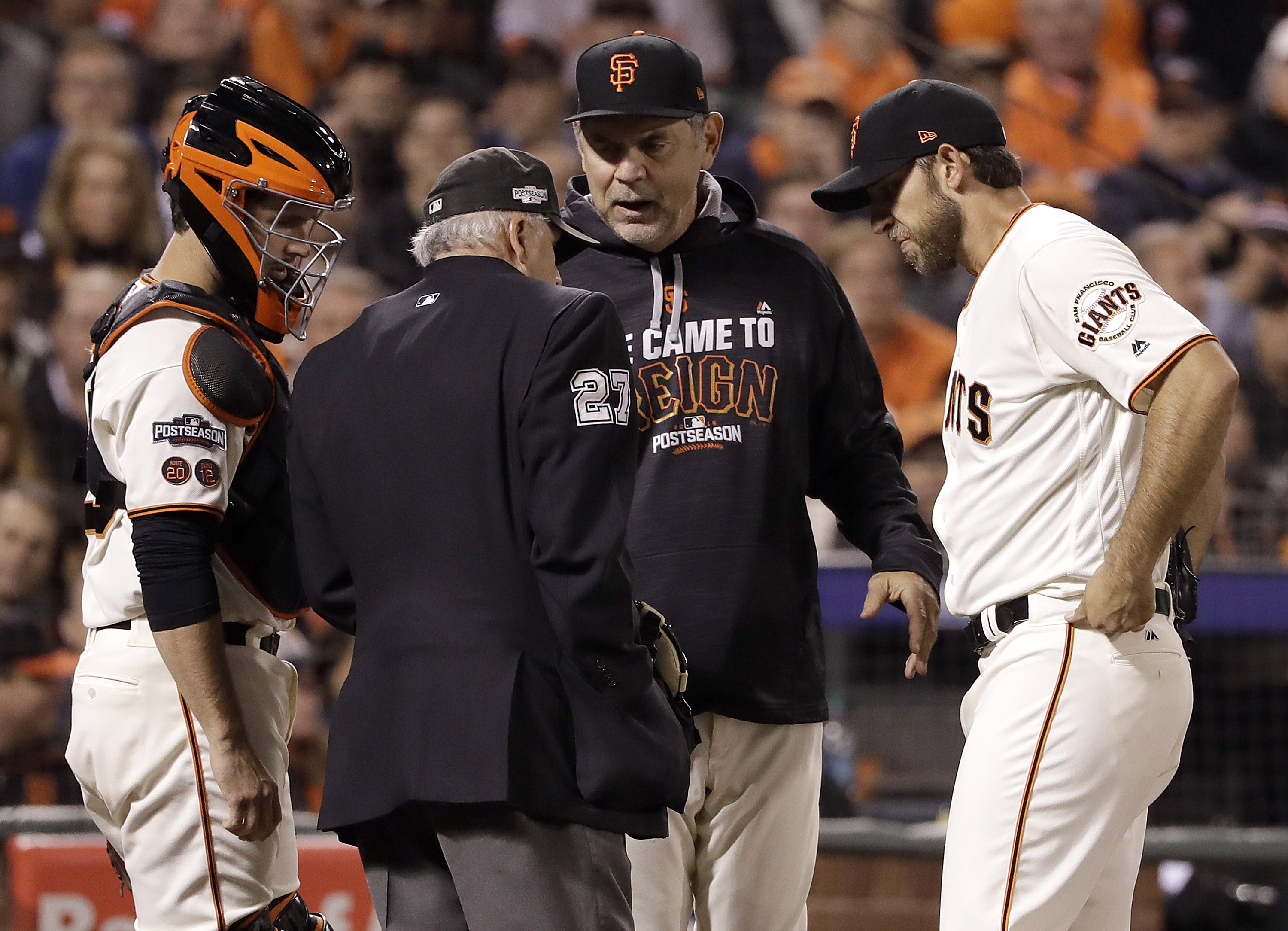 Home plate umpire Larry Vanover (27) talks with San Francisco Giants catcher Buster Posey, from left, manager Bruce Bochy and pitcher Madison Bumgarner during the second inning of Game 3 of baseball's National League Division Series between the Giants and