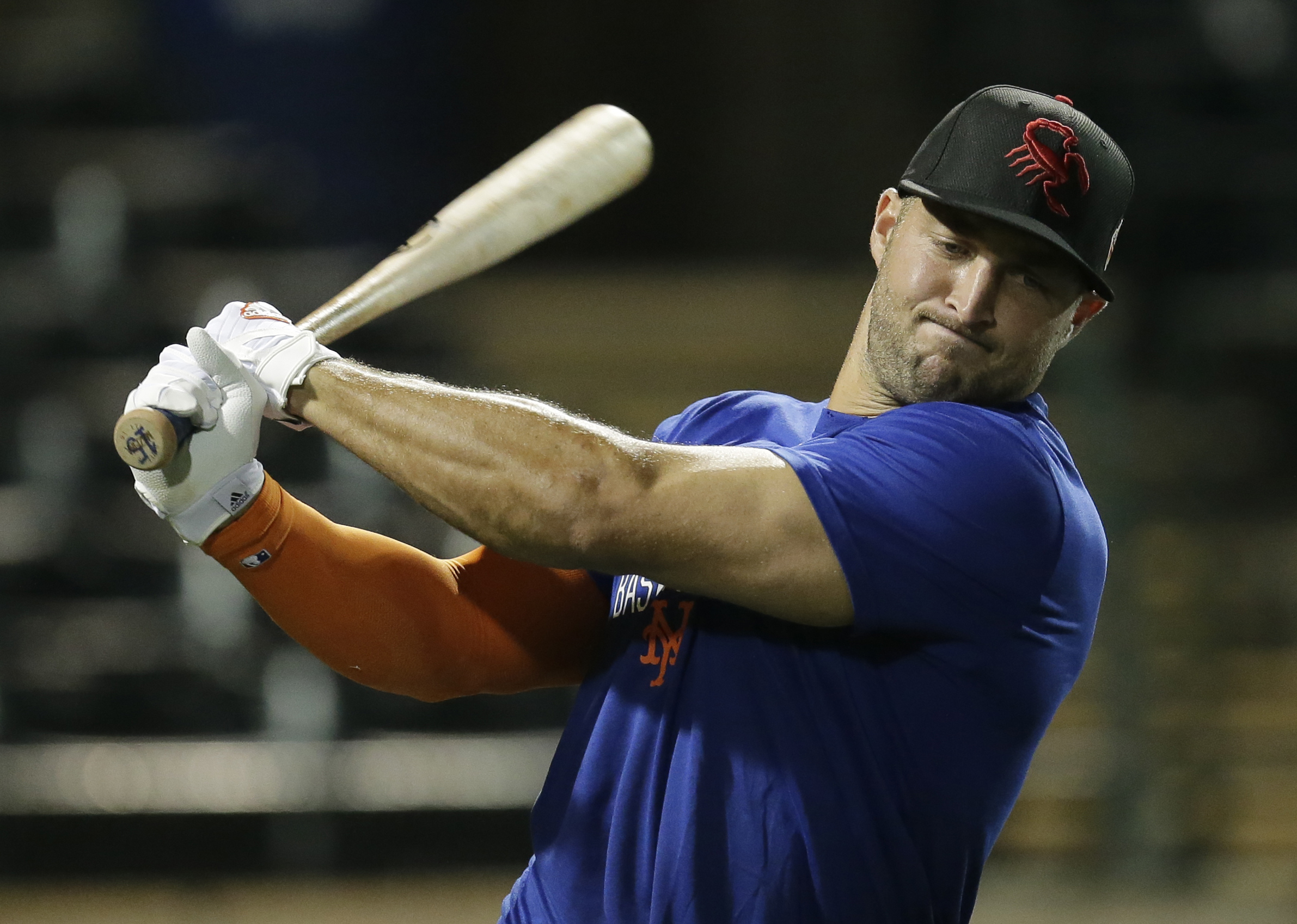 Former NFL quarterback Tim Tebow warms up before baseball practice for the Arizona Fall League, Monday, Oct. 10, 2016, in Scottsdale, Ariz. (AP Photo/Rick Scuteri)