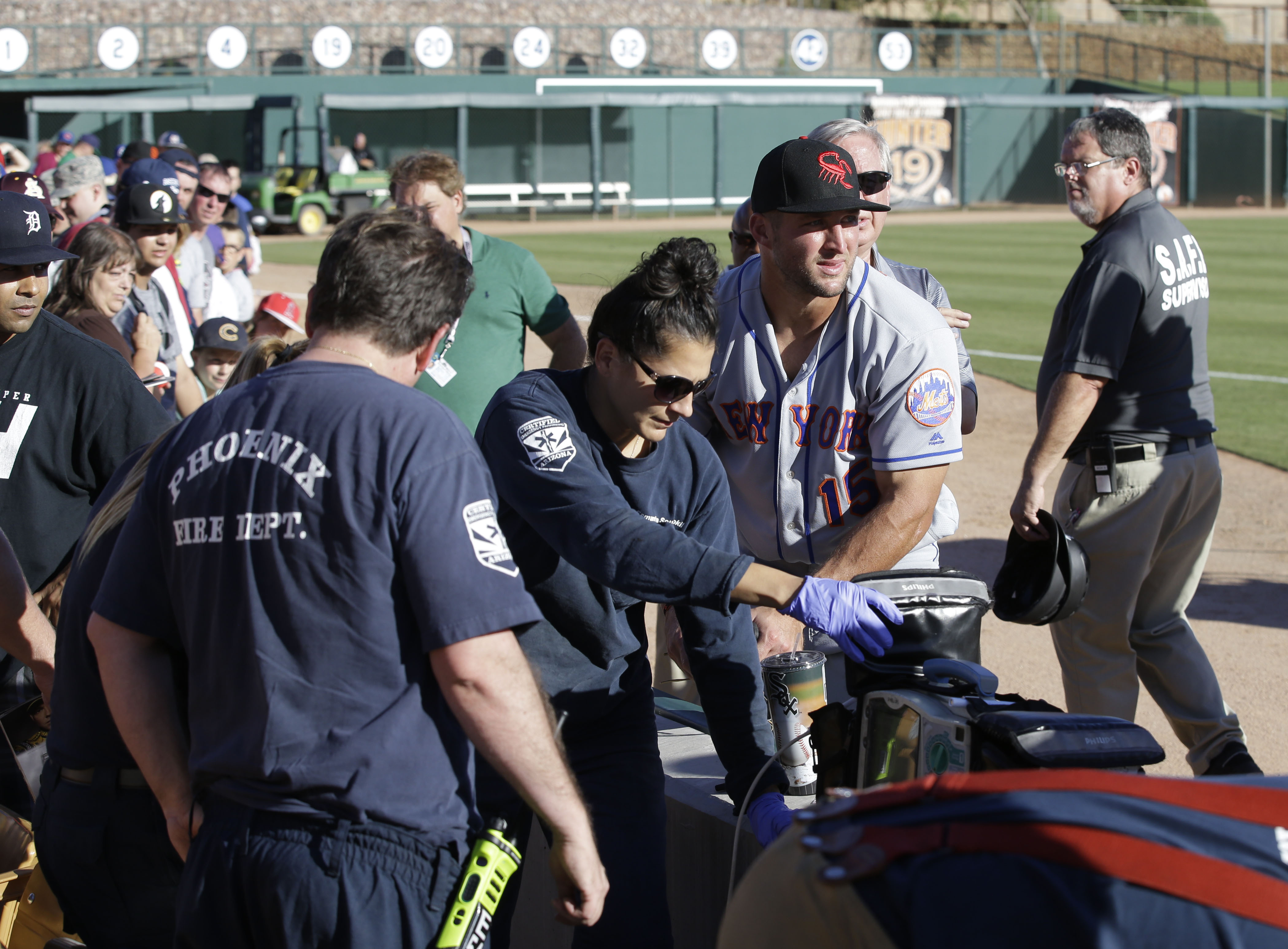 Scottsdale Scorpions outfielder Tim Tebow, center, comforts a fan, on ground, who was suffering a seizure, following Tebow's debut against the Glendale Desert Dogs in a baseball game Tuesday, Oct. 11, 2016, during the Arizona Fall League in Glendale, Ariz