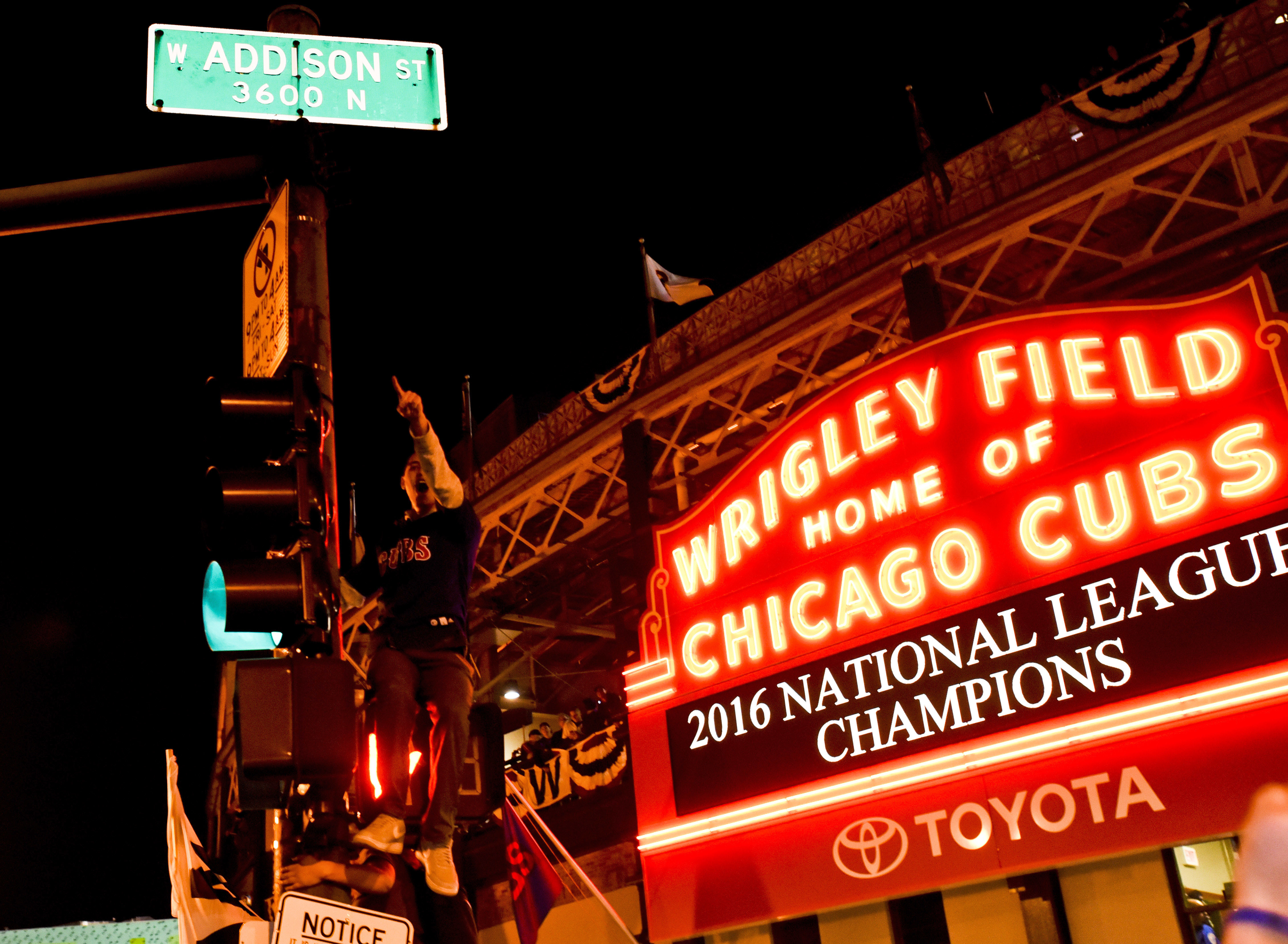 Chicago Cubs fans celebrate outside Wrigley Field after the Cubs defeated the Los Angeles Dodgers 5-0 in Game 6 of baseball's National League Championship Series, Saturday, Oct. 22, 2016, in Chicago. The Cubs advanced to the World Series. (AP Photo/Matt M
